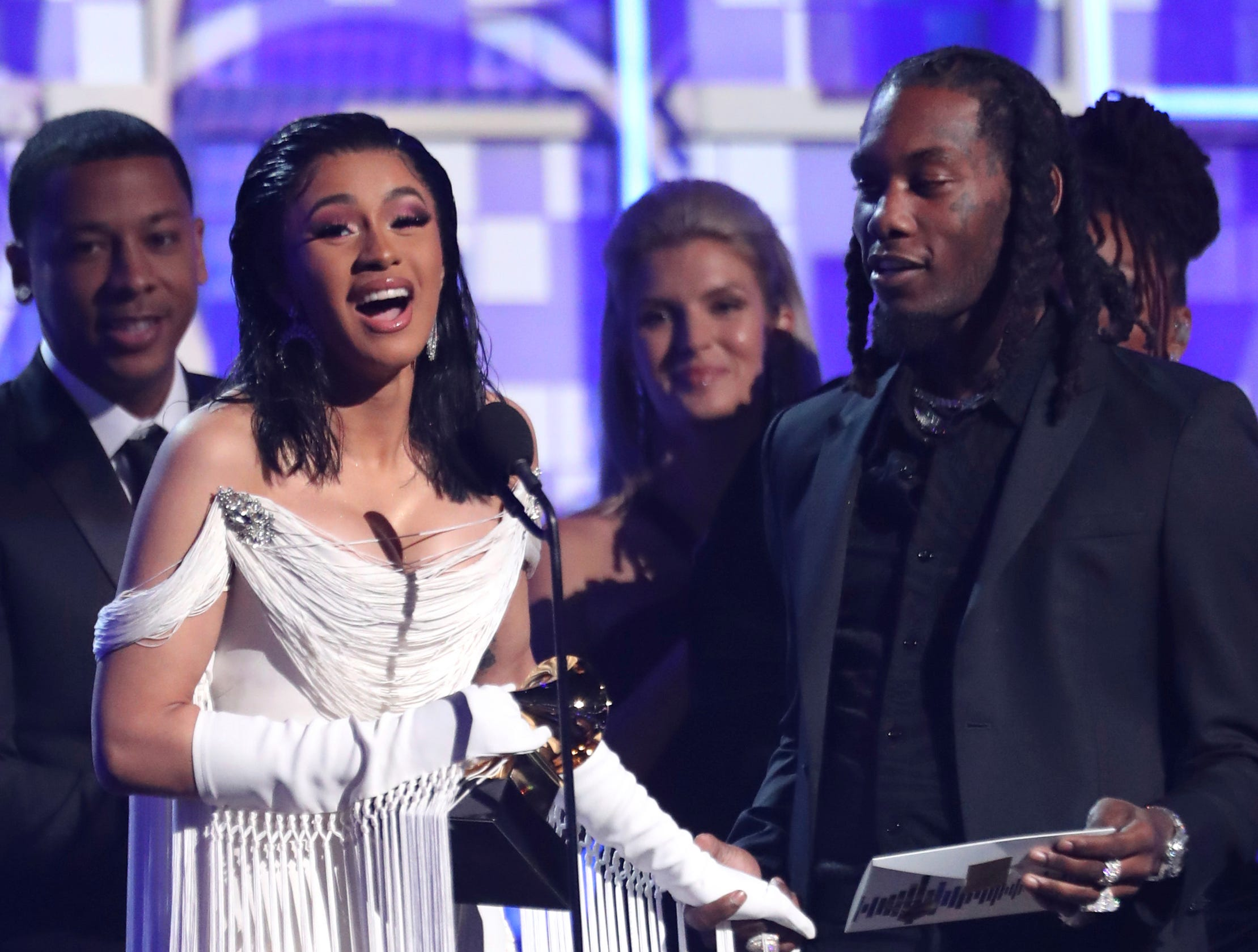 "Cardi B, left, accepts the award for best rap album for ""Invasion of Privacy"" as Offset looks on at the 61st annual Grammy Awards."