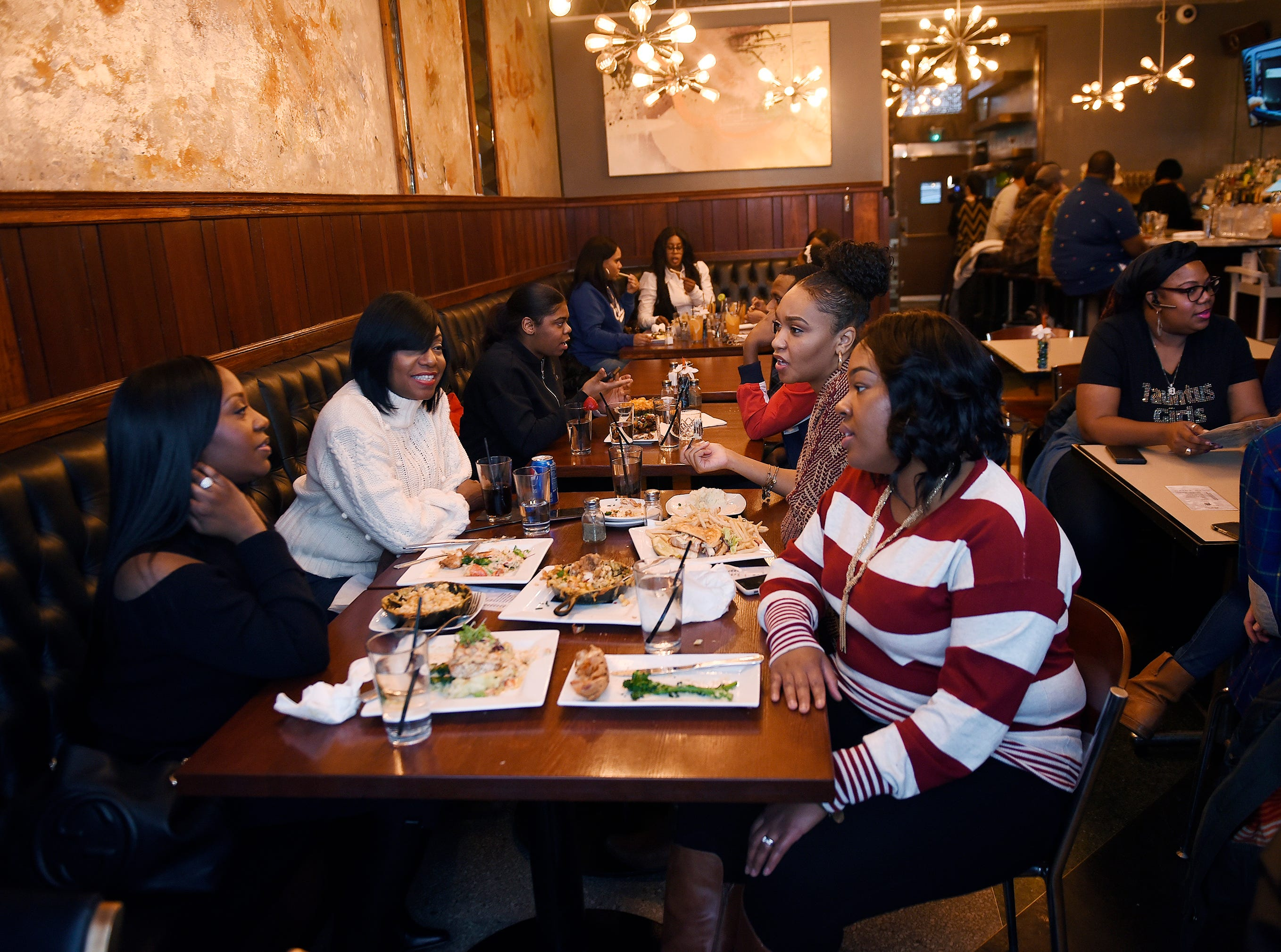 l-r, foreground, Tanisha Berry, (blk top), 31, of Livonia who is celebrating her birthday with friends Ericka Wimbley, (red & white sweater) 30, of Westland, Grace Wimbley, (white sweater), 41,of Redford and Chimere Dodson,(29, ponytail), of Lansing enjoy their conversation during dinner.