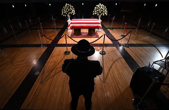 A Dearborn police officer stands in front of the casket of retired U.S. Rep. John D. Dingell Monday in Dearborn.