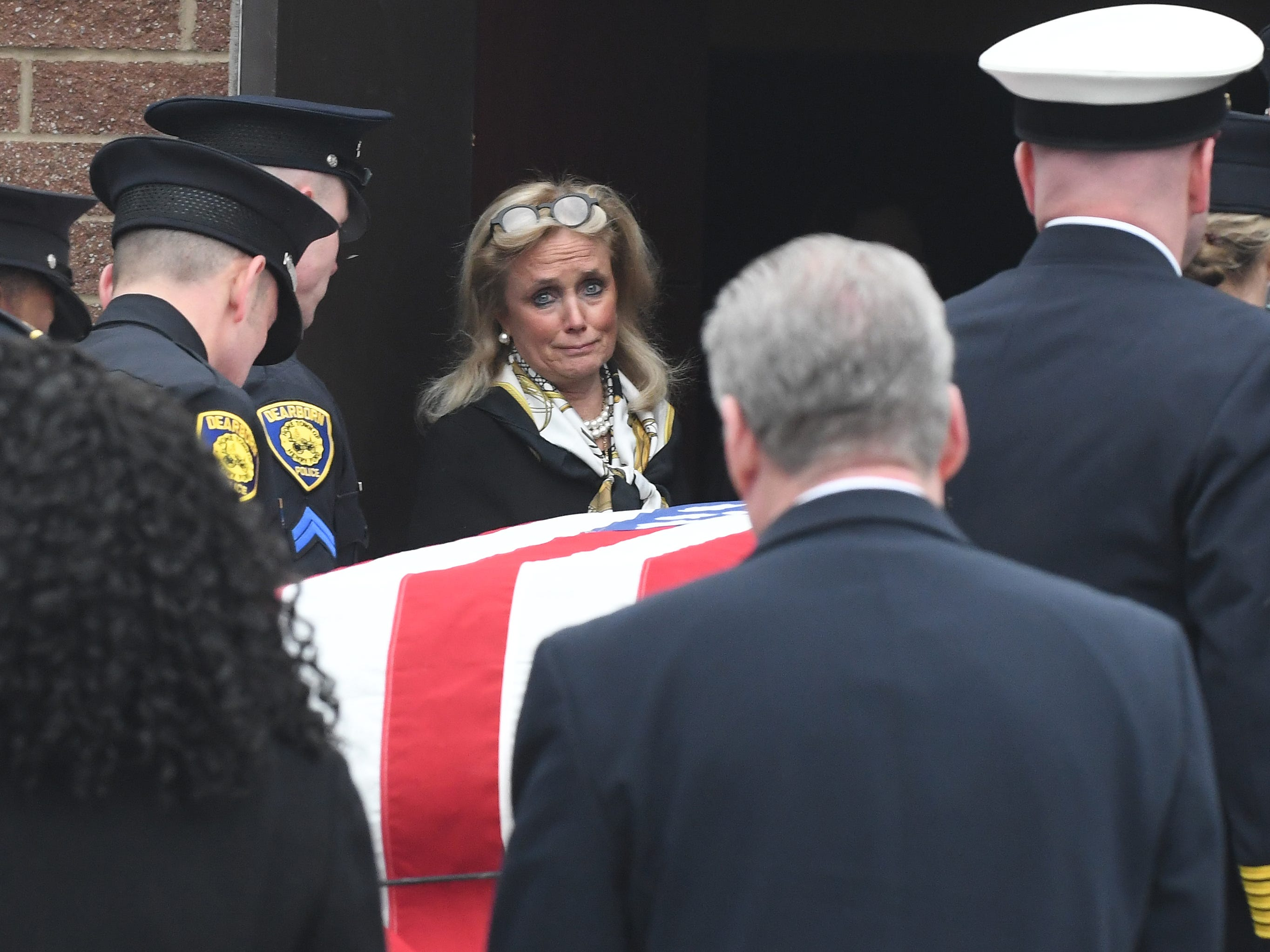 U.S. Rep. Debbie Dingell waits at the door as the casket of her husband, retired U.S. Rep. John D. Dingell, arrives for the public viewing Monday at the Ford Community and Performing Arts Center in Dearborn.