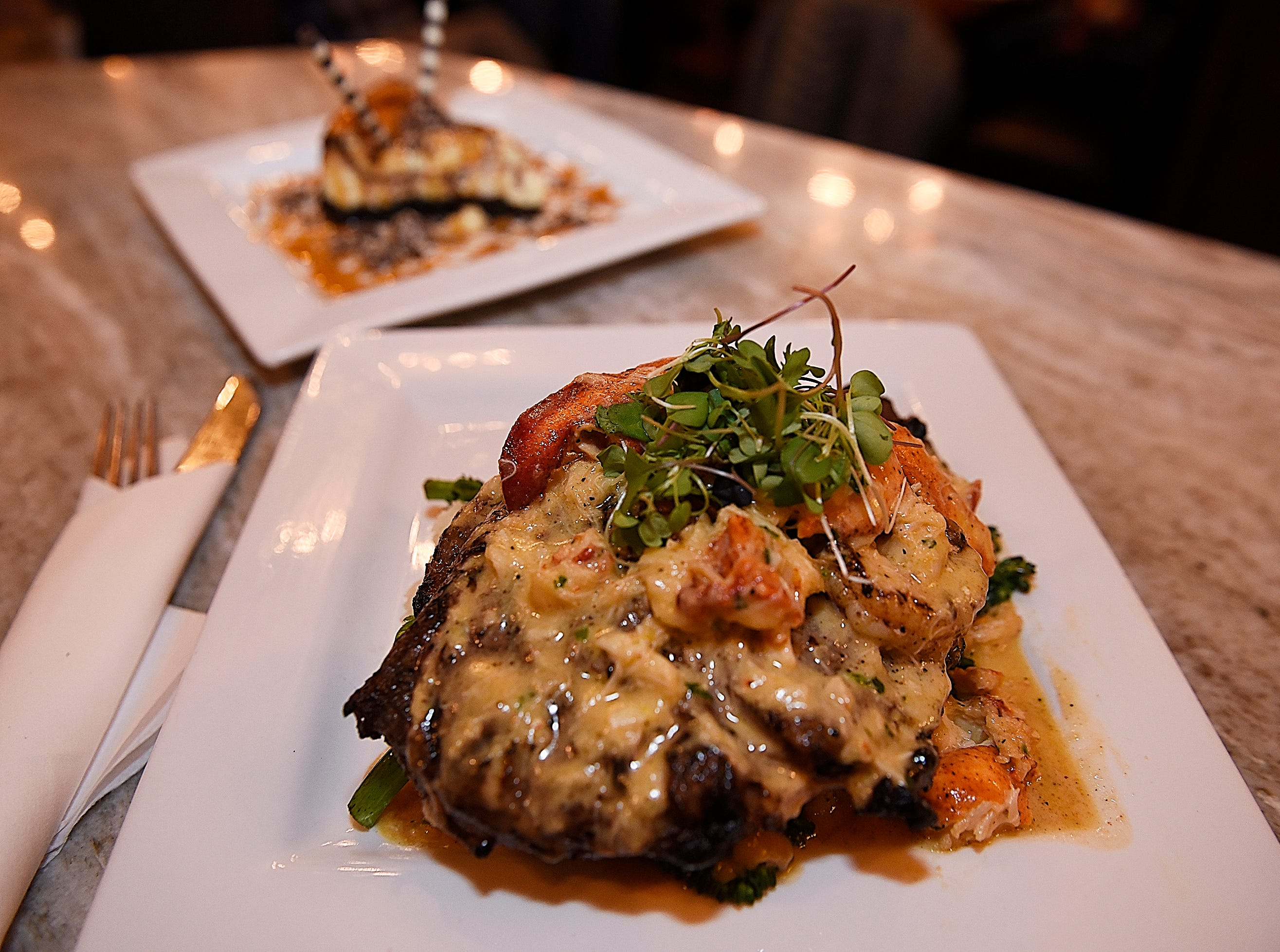 A plate of the Oscar de Le' Culture, (grass-fed Angus ribeye with broccolini, jumbo lump crab, rock lobster tail and whipped mash potatoes) with a plate of the Black Bottom Cheesecake in the background.