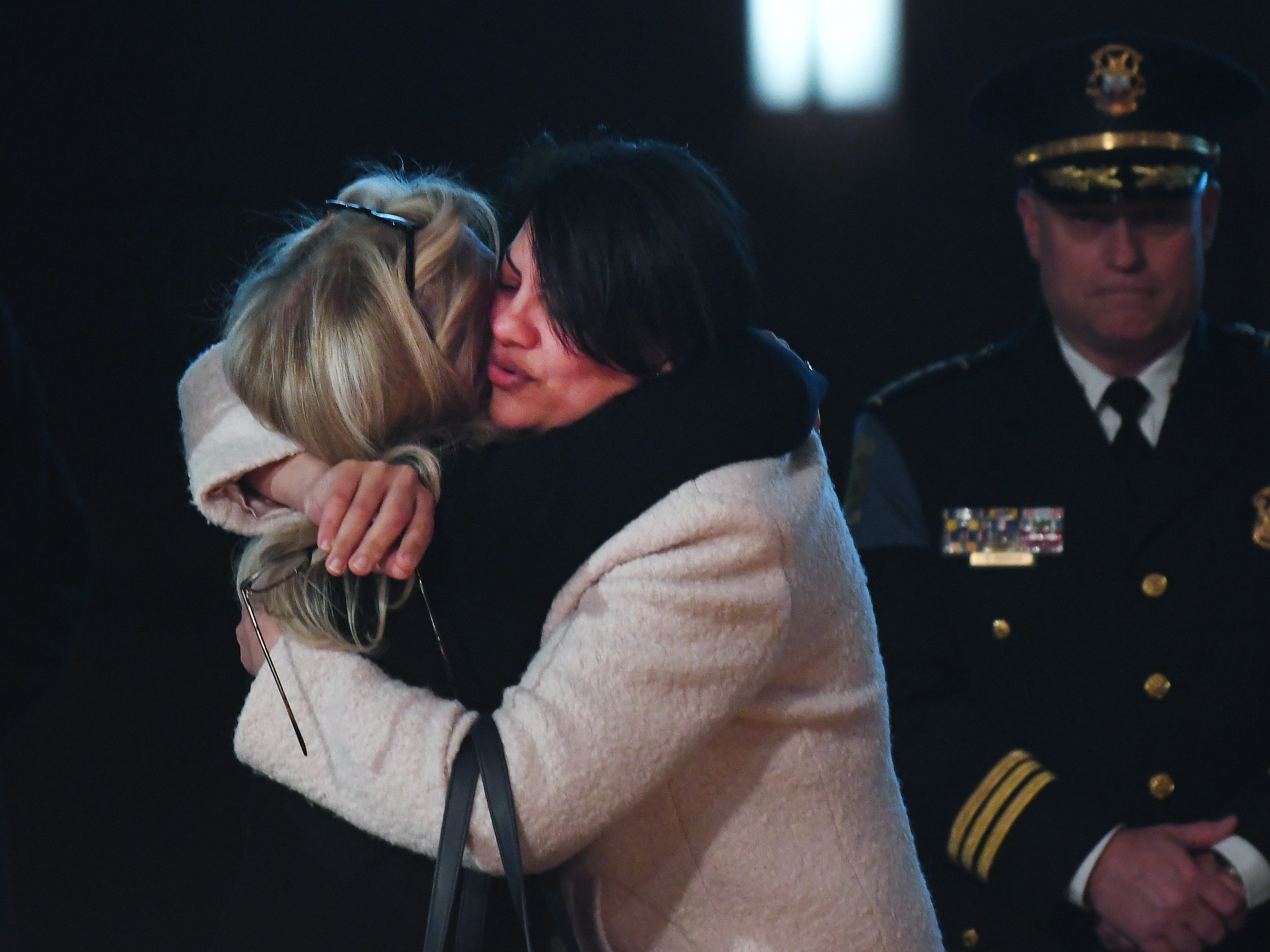 Reps. Debbie Dingell, left, and Rashida Tlaib embrace during the public viewing of the casket of retired Rep. John D. Dingell.