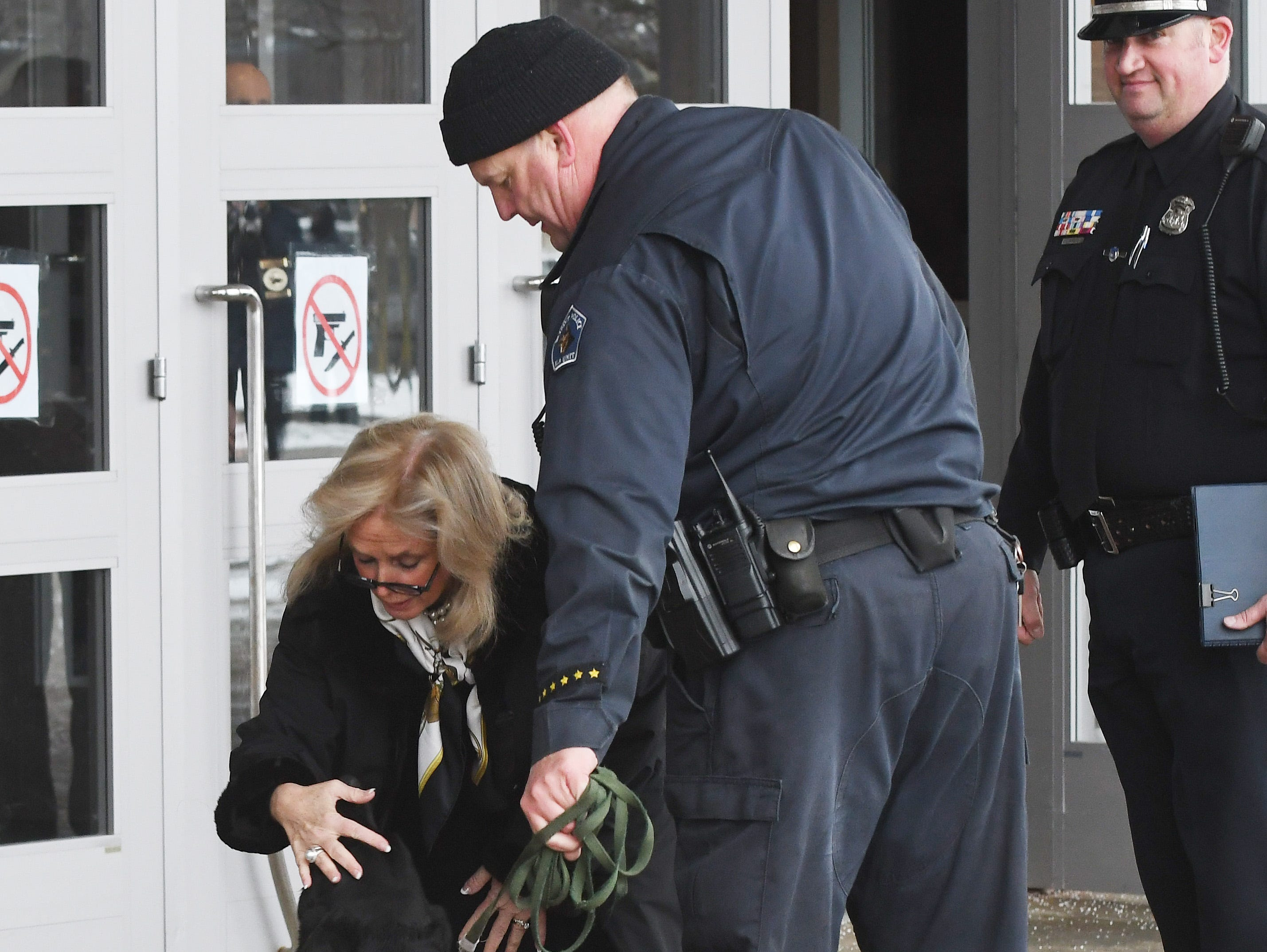 Debbie Dingell arrives, stopping to pet a Dearborn police dog, before the public viewing begins.