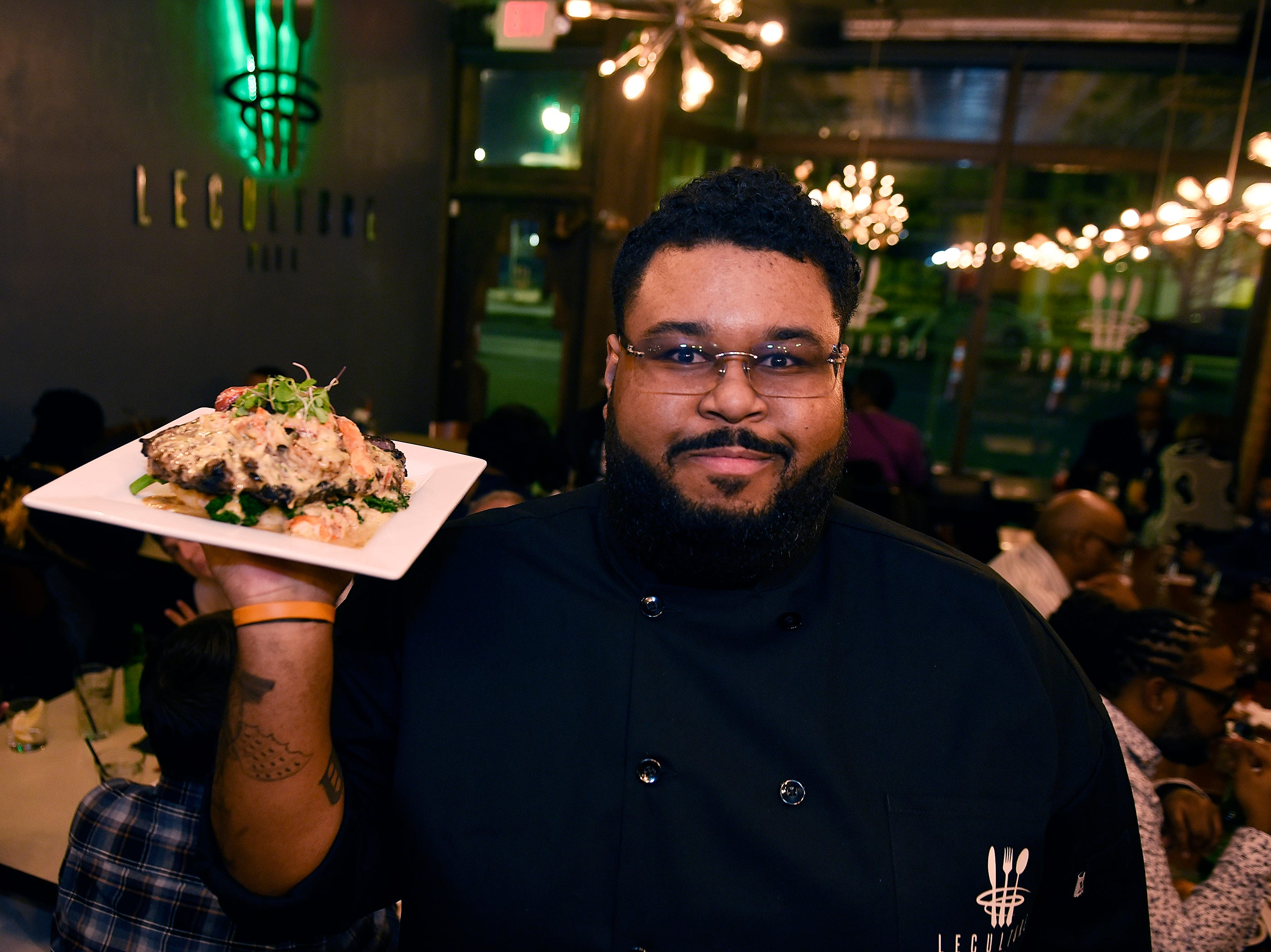 Drew Matthews, owner and executive chef of Le  Culture Cafe holds a plate of the Oscar de Le' Culture (20 ounce Angus ribeye with broccolini, jumbo lump crab, rock lobster tail and whipped mash potatoes) in the main dining area.
