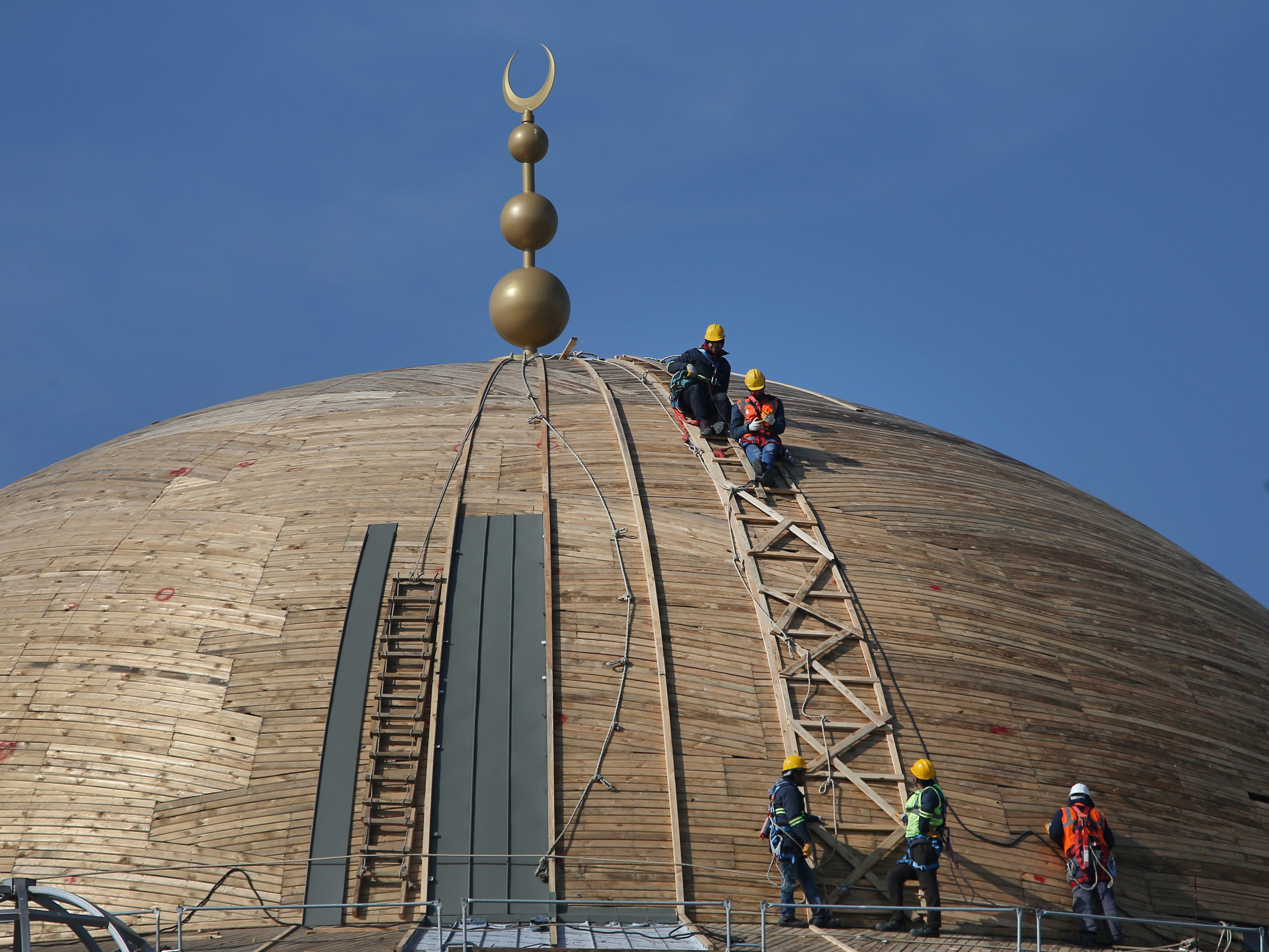 Laborers work at the dome of a mosque under construction in Istanbul, Monday, Feb. 11, 2019. The mosque in the historic Taksim square of Turkey's largest city began to take shape in 2017, is expected to open for prayers this year.