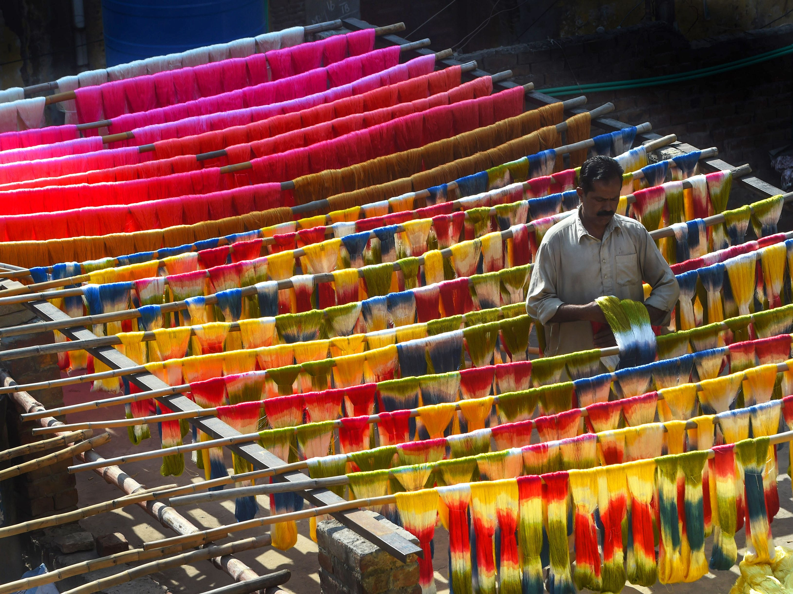 A Pakistani worker dries fabric threads after dyeing them at a factory in Lahore on Feb. 11, 2019.