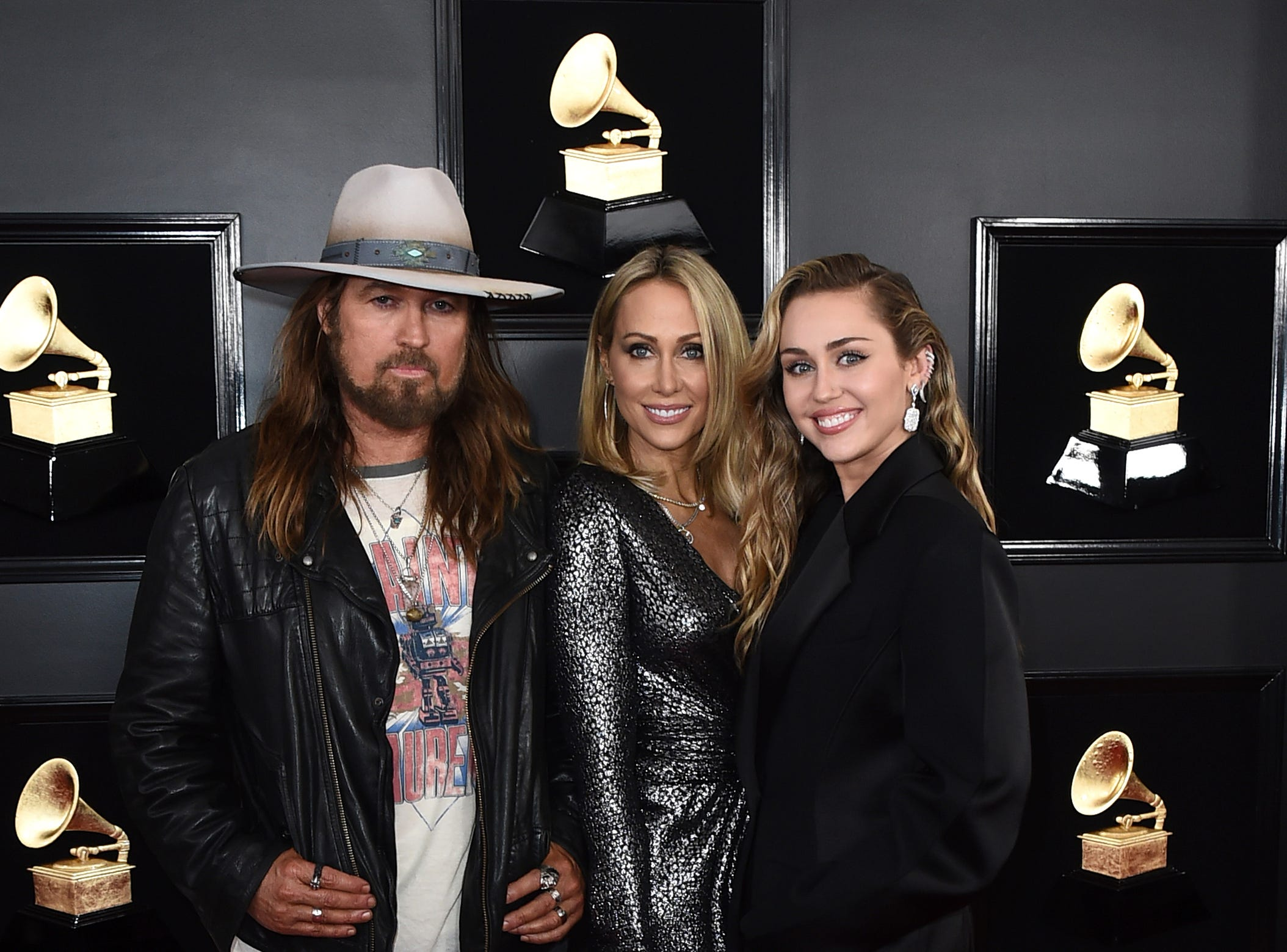 Billy Ray Cyrus, from left, Tish Cyrus, and Miley Cyrus arrive at the 61st annual Grammy Awards at the Staples Center.
