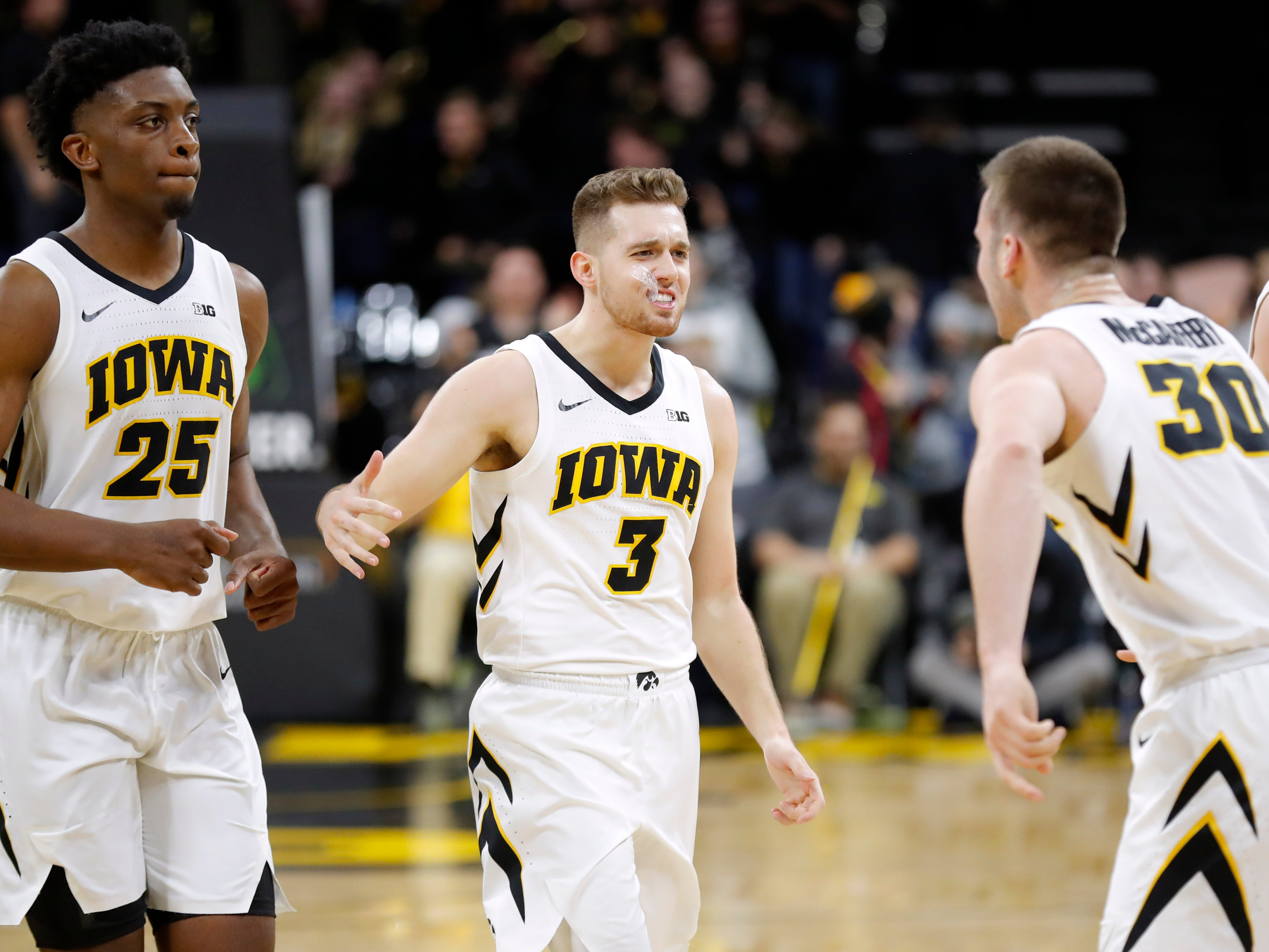Iowa guard Jordan Bohannon (3) celebrates with teammates Tyler Cook, left, and Connor McCaffery, right, after an NCAA college basketball game against Northwestern, Sunday, Feb. 10, 2019, in Iowa City, Iowa. Bohannon made a three-point basket at the end of the game as Iowa won 80-79. (AP Photo/Charlie Neibergall)
