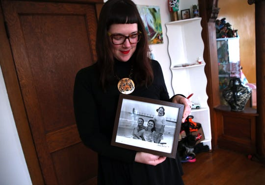 Morgan Richardson is seen at home in Chicago on Tuesday, Jan. 29, 2019, with a photo of herself with her twin sister Lauren, left, and mother Deborah. Richardson, who was conceived via In Vitro Fertilization (IVF), submitted a DNA sample to the DNA testing company 23andMe to find out about her ancestry. Almost immediately, she started discovering half-siblings from across the U.S., all from the same anonymous sperm donor her mom used. (Terrence Antonio James/Chicago Tribune)