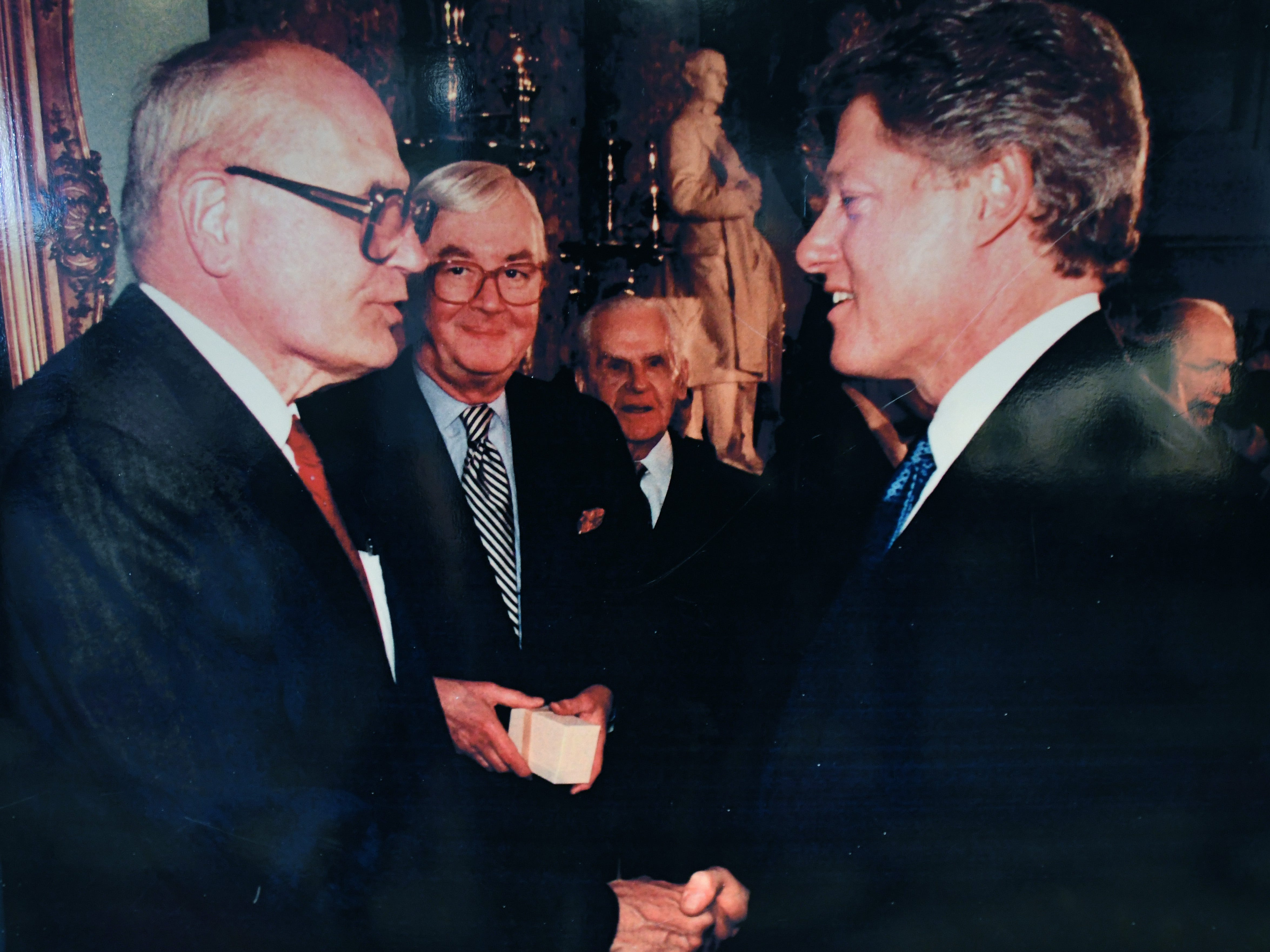 John Dingell shakes hands with President Bill Clinton as Sen. Daniel Patrick Moynihan of New York looks on.