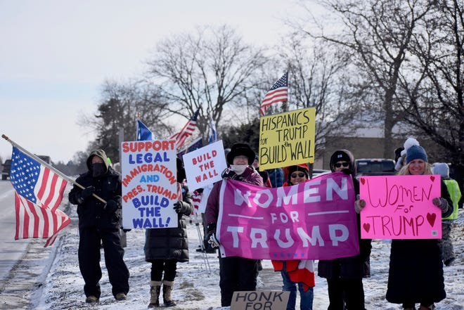 """Protesters from various groups, including """"Women for a Safe America"""" and """"Women for Trump,"""" line Woodward Avenue for a """"Build the Wall"""" rally at the Oakland County Republican Party offices in Bloomfield Hills, Mich. on Jan. 26, 2019."""