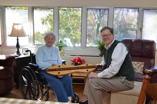 "Betty Tarr, an independent living resident at Wesley Woods Towers, is shown here chatting with her son Sam about a handmade dulcimer that was a gift from her late husband. She didn't wait for her children to have ""the talk"" with her about moving from her home in Hartwell. She knew it was no longer safe for her to live alone. Photo: Contributed by Dan Curran/Atlanta Journal-Constitution/TNS)"