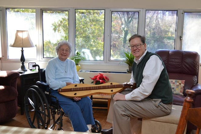 """Betty Tarr, an independent living resident at Wesley Woods Towers, is shown here chatting with her son Sam about a handmade dulcimer that was a gift from her late husband. She didn't wait for her children to have """"the talk"""" with her about moving from her home in Hartwell. She knew it was no longer safe for her to live alone. Photo: Contributed by Dan Curran/Atlanta Journal-Constitution/TNS)"""