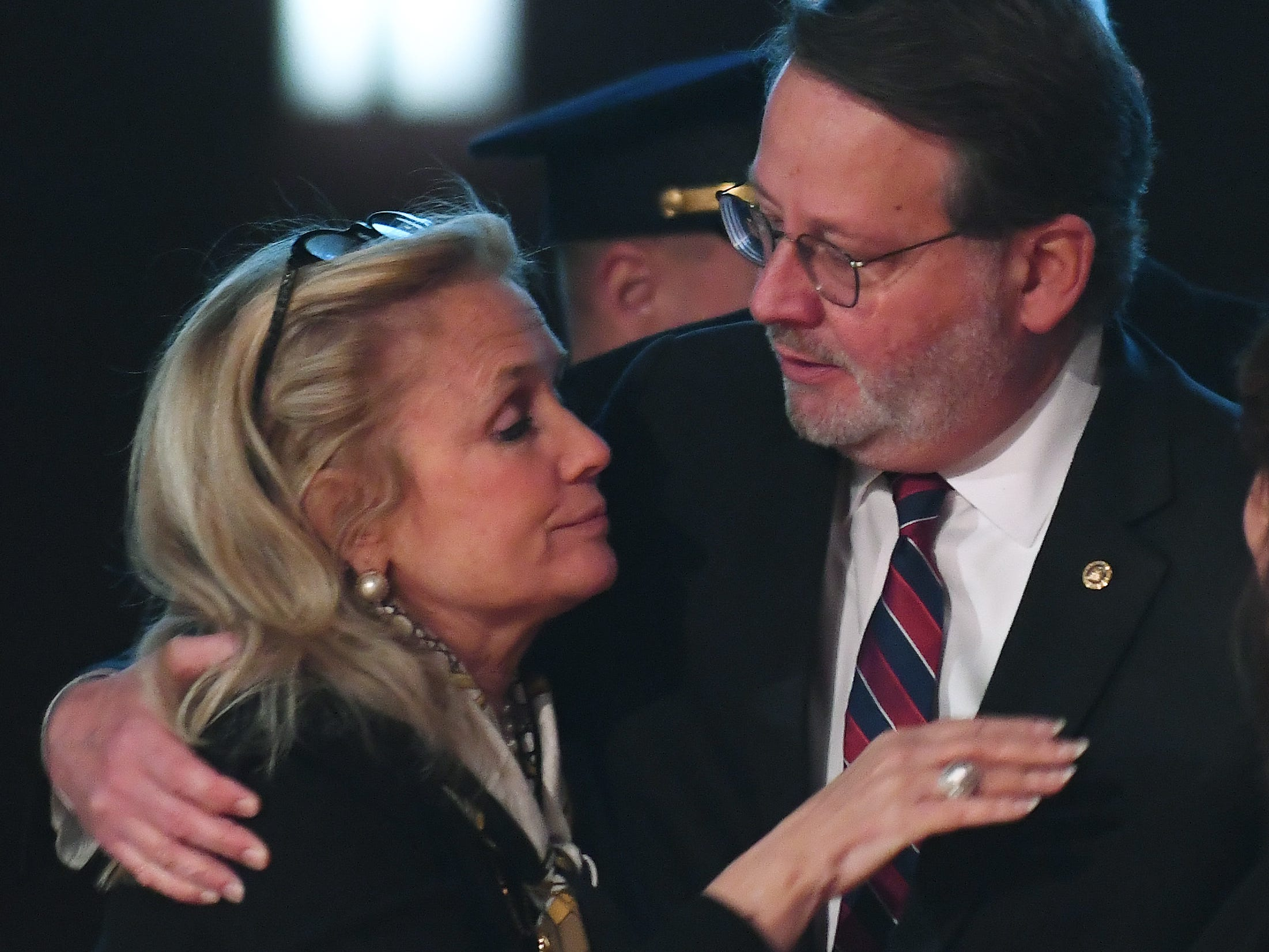 U.S. Rep. Debbie Dingell hugs U.S.. Sen. Gary Peters during the public viewing of the casket of her husband, retired Rep. John D. Dingell.