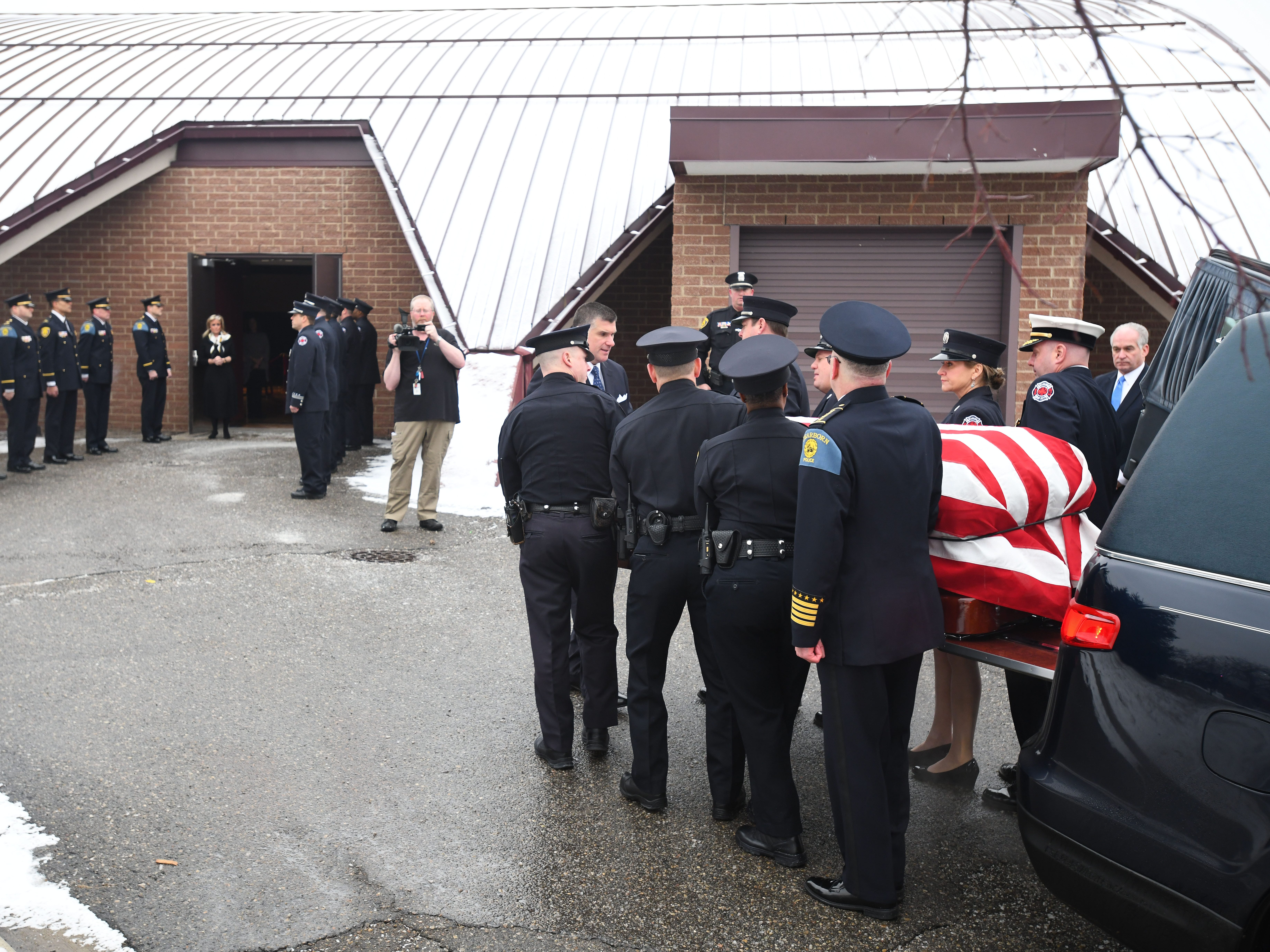 Dearborn public safety officers take John Dingell's casket into the Ford Community and Performing Arts Center in Dearborn.