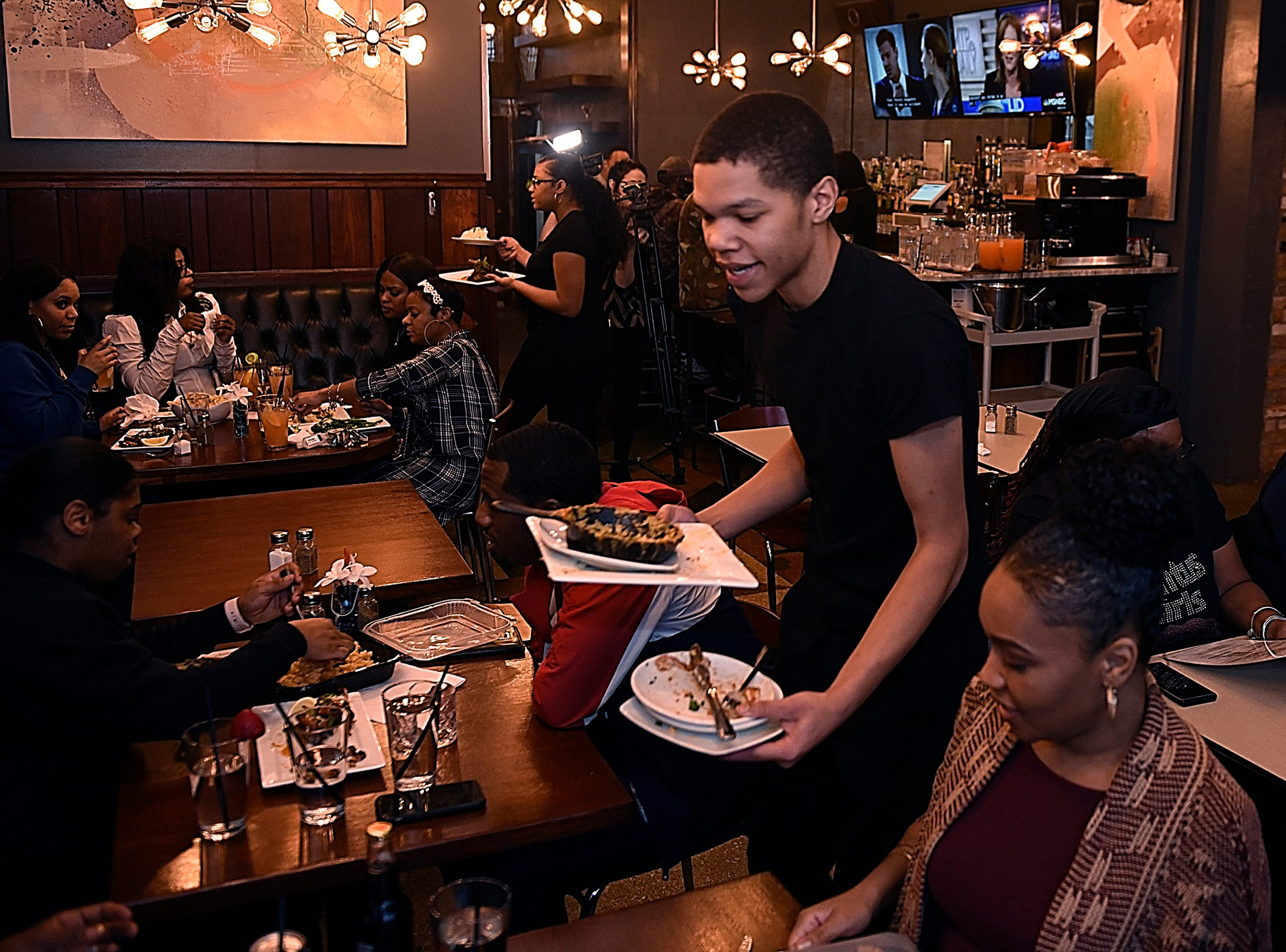 Server, Jordan Sumler, 18, serves dinner plates to customers.