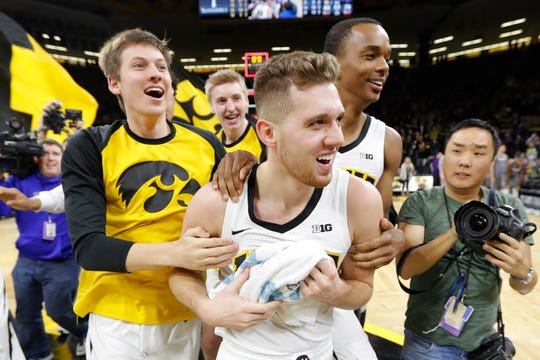 Iowa guard Jordan Bohannon, center, celebrates with teammates after Sunday's win over Northwestern.