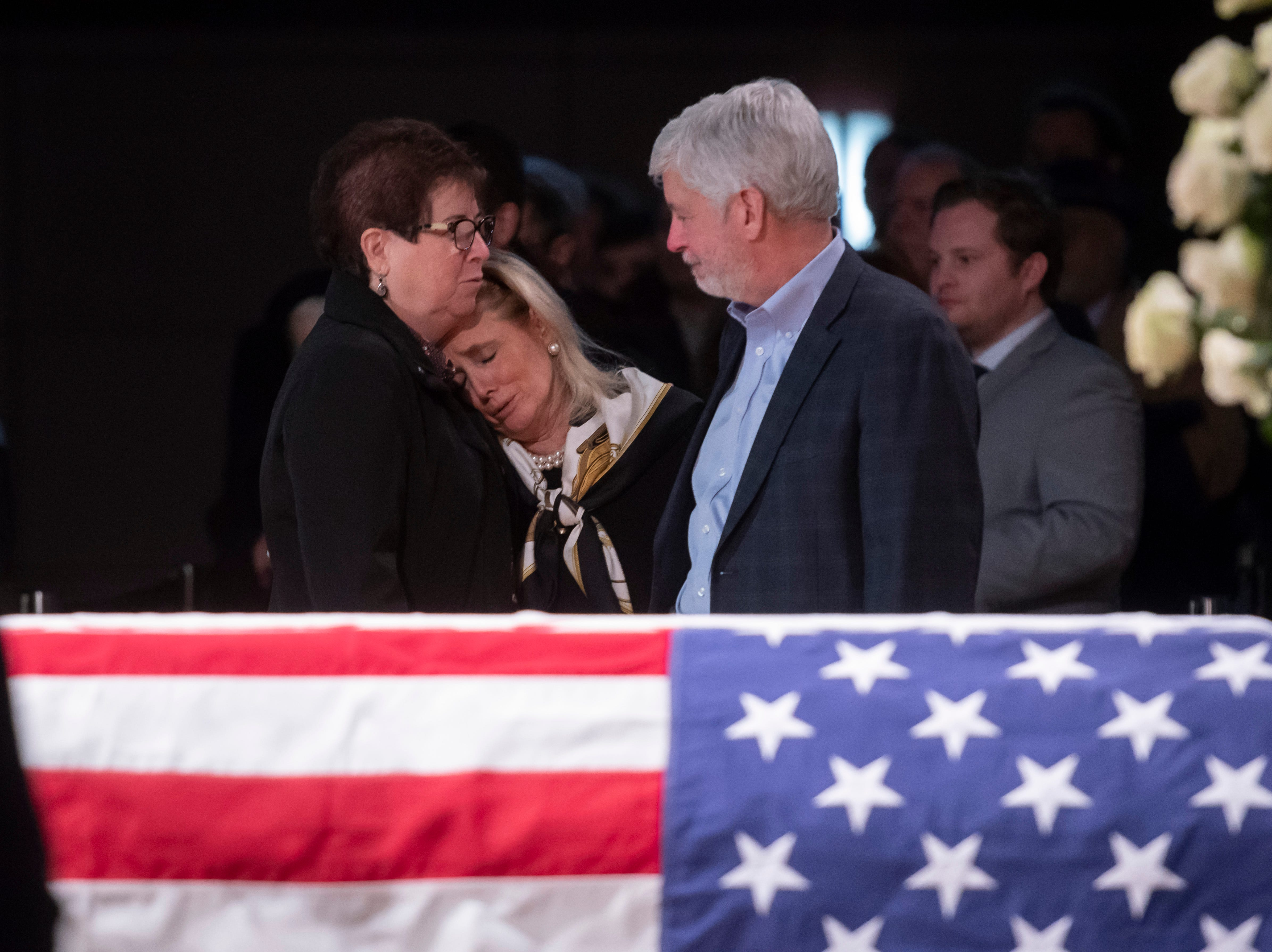 U.S. Rep. Debbie Dingell, center, is consoled by former Michigan Governor Rick Snyder, right, and his wife Sue during the  visitation for her husband, former U.S. Rep. John Dingell at the Ford Community and Performing Arts Center, in Dearborn, February 11, 2019.