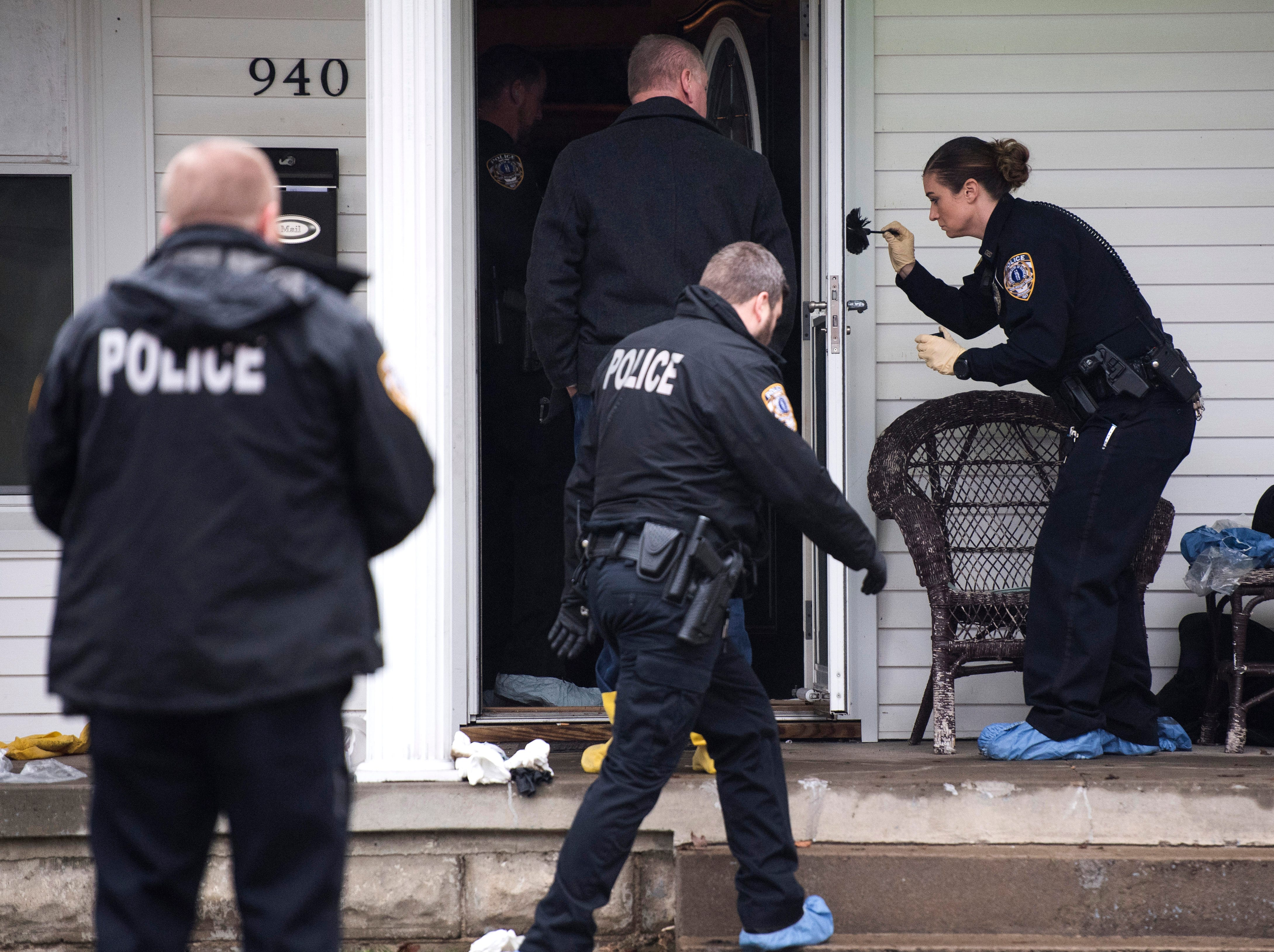 OPD officer Jennifer Haynes, far right, dust for finger prints on the outside of a screen door at 940 Audubon Avenue in Owensboro, Ky.  as police investigate a fatal shooting with at least four victims, Thursday Jan. 17, 2019.