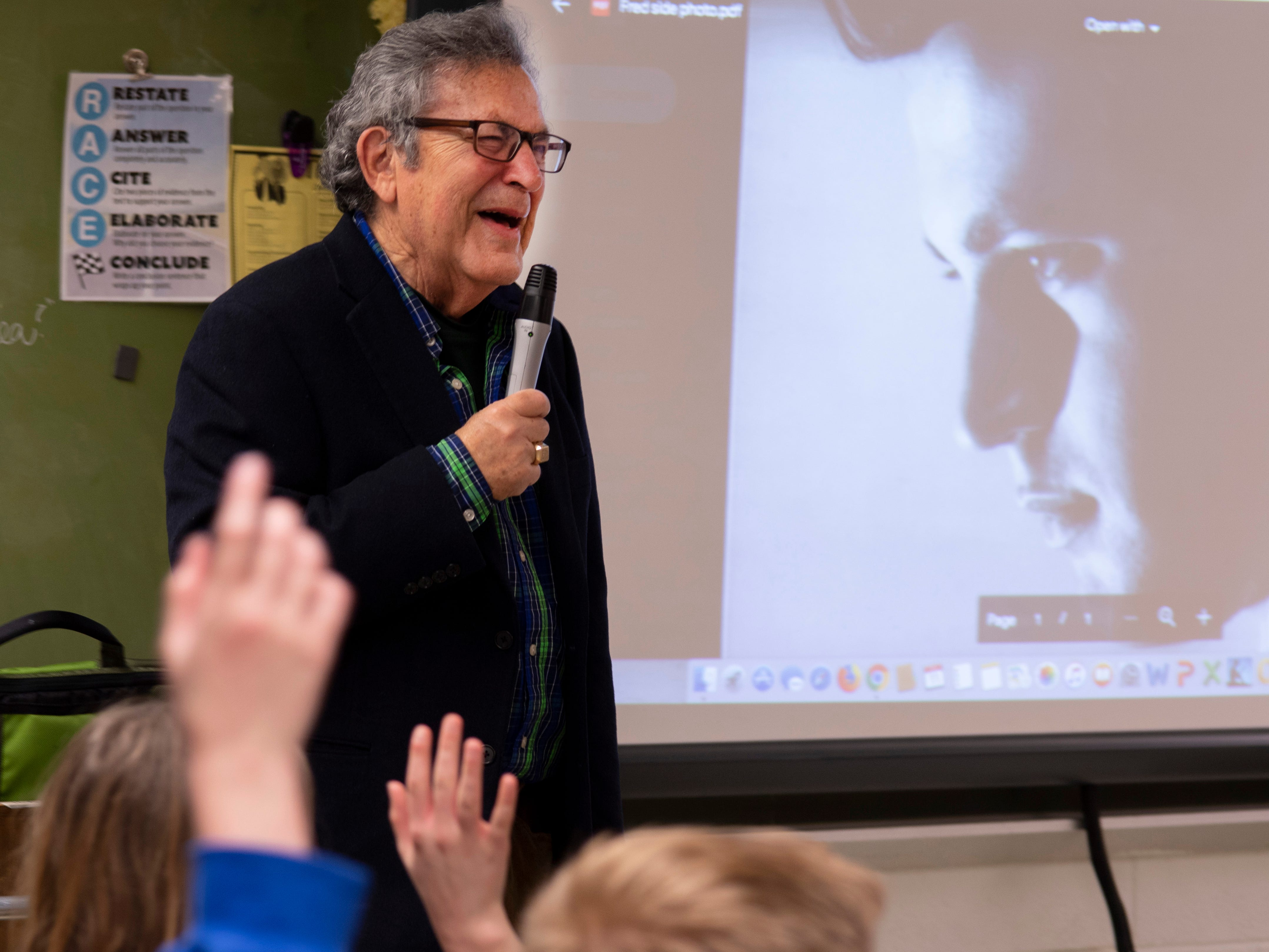 Fred Gross is tickled by a past picture of him during his younger acting days as he speaks to Rebekah Hodges' Thompkins Middle School class Monday morning. Gross, a Jewish Holocaust survivor, and his family stayed one step ahead of the Nazis to eventually arrive safely in the United States in 1946.