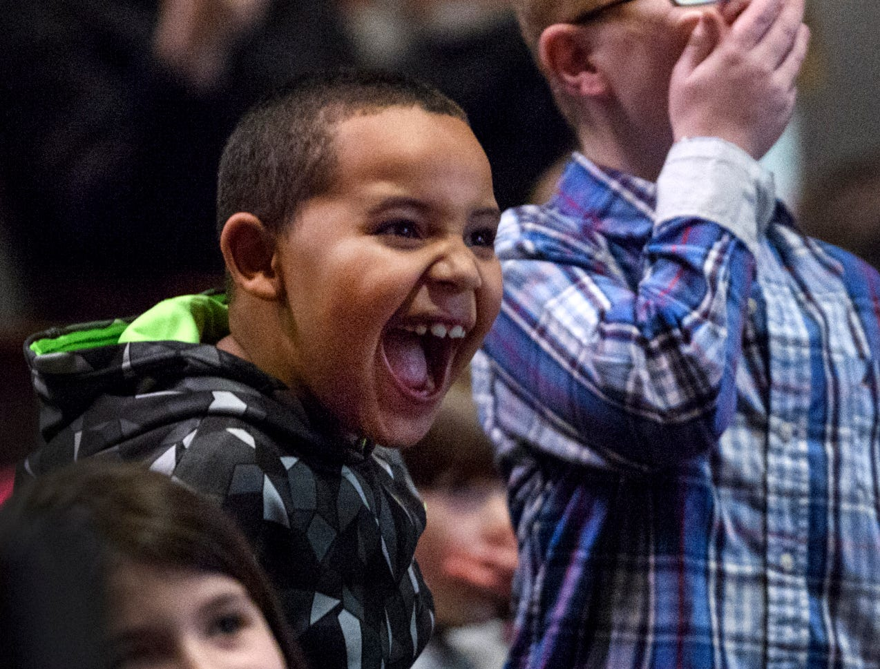 Cassius Prather, 6, front, and James Patterson, 8, back, react to Lisa Hoffman of John James Audubon State Park, not pictured, pulling a live Barred Owl out of a cage during a Henderson County Public Schools Family Night inside Henderson Community College's Preston Arts Center, Thursday, Jan. 24, 2019.