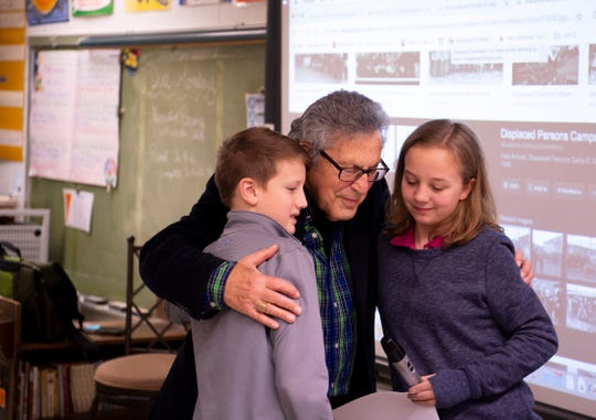 Fred Gross of Louisville, Ky., hugs Thompkins Middle School students Daniel Hartz, left, and Hannah Brown, both 11, after the read a poem the class had written about Gross's escape from Hitler's Nazis Monday morning.