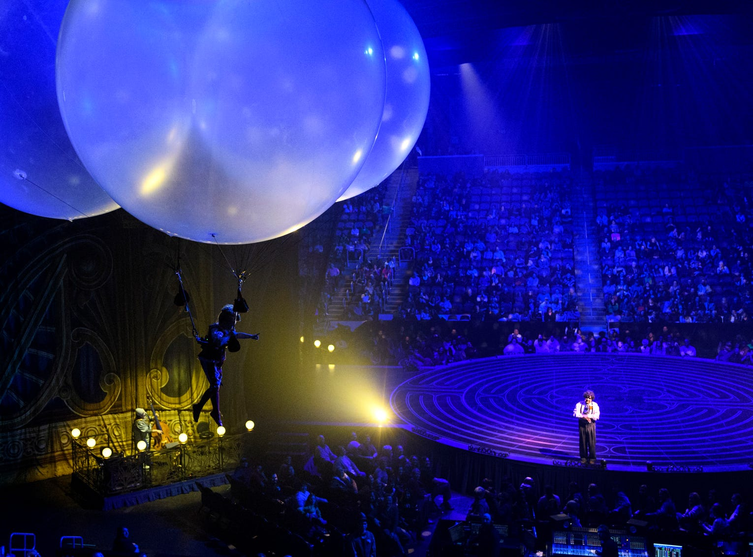 Valentyna Pahlevanyan, left, leaves Mauro the Dreamer Clown, played by Lolo Fernández, on stage to float around the crowd using inflatable balloons during Cirque du Soleil's Corteo show at Ford Center in Evansville, Ind., Wednesday night, Jan. 23, 2019. The crowd was encouraged to interact with her by using their hands to push her around the arena and then back to the stage before the end of the act.