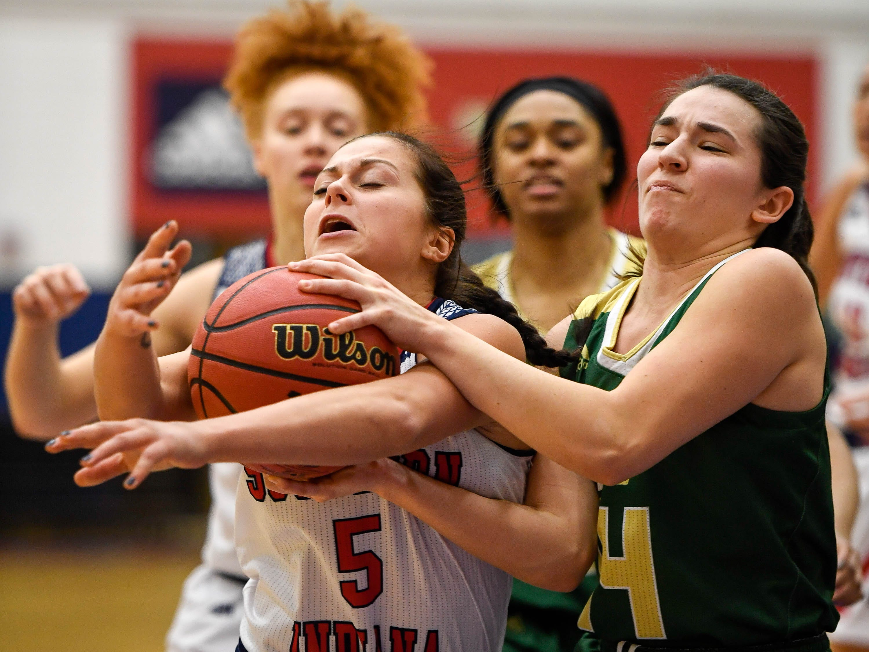 Missouri S & T's Jordan Kabetske (14) gets a held ball on University of Southern Indiana's Milana Matias (5) as she drives the ball as the University of Southern Indiana Women Screaming Eagles play the Missouri Science & Technology Miners at the PAC Arena Thursday, January 24, 2019.