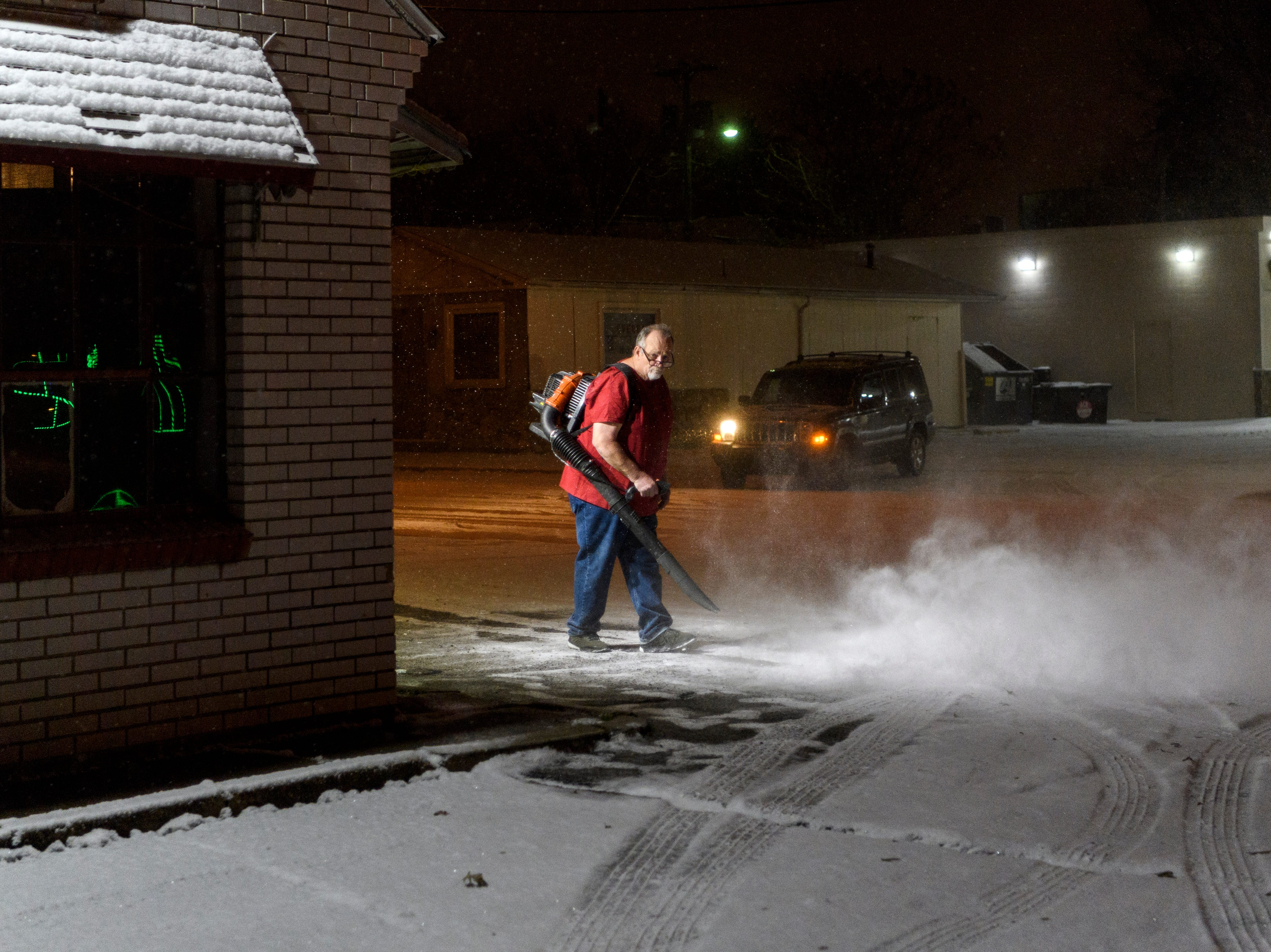 "Mike Harmes of Harmes Una Pizza uses a leaf blower to clear fresh snow off the restaurant's parking lot at the corner of South Kentucky and Washington Streets in Evansville, Ind., to make it easier for customers to come in, Tuesday evening, Jan. 29, 2019. ""I've been cooped up [in a hot kitchen] all night, feels good to be out here for a few moments,"" Harmes said, when asked why he wasn't wearing a jacket."