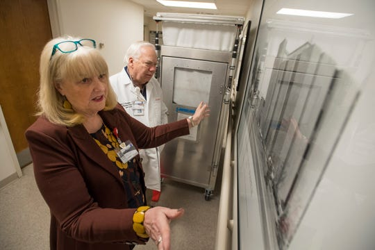 Chief nursing officer Donna Poduska shows a historic photo of what the hospital looked like when she started while her husband, infection preventionist Paul Poduska, looks on on Friday, Feb. 8, 2019, at UCHealth Poudre Valley Hospital in Fort Collins, Colo.