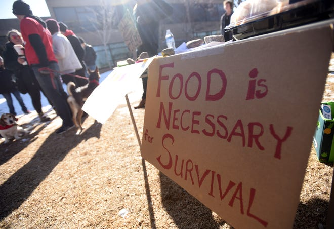 Crowds gather as food is set out during a lunch for the homeless on Sunday, Feb 10, at Library Park in Old Town Fort Collins, Colorado.