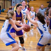 Jenna Hornblad and Hallie Wusterbarth apply pressure to Sara Dax of Kewaunee as she drives to the basket on a fast break in their game on Friday.