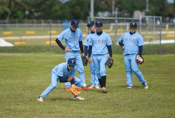 Yeoju University baseball players anticipate ground balls during a drill at the Guam Sports Complex in Dededo, Feb. 11, 2019.