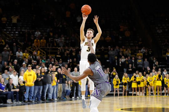 "Iowa point guard Jordan Bohannon rises up for the game-winning 3-pointer over Northwestern guard Anthony Gaines on Sunday at Carver-Hawkeye Arena. ""I knew it was good before it even left my hand,"" Bohannon said,"