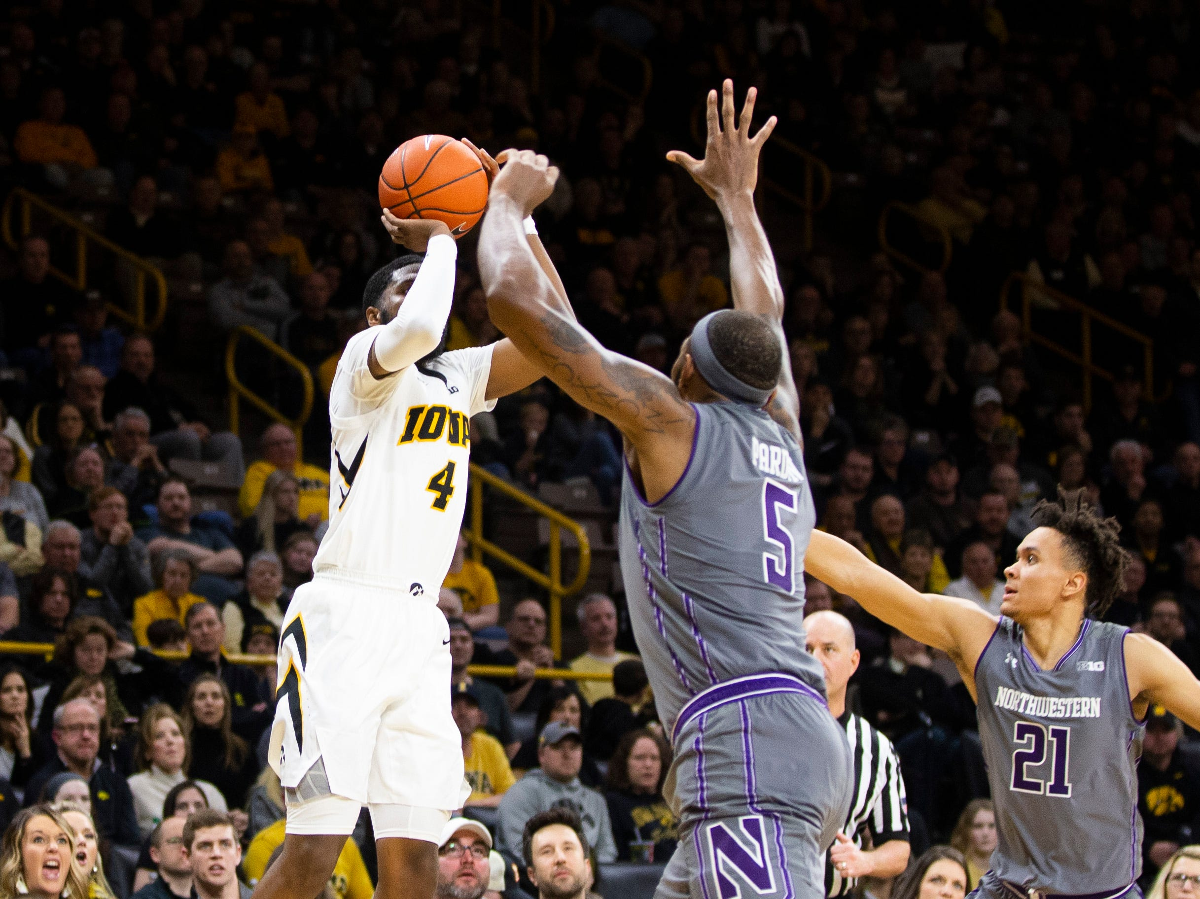 Iowa guard Isaiah Moss (4) makes a 3-point basket while Northwestern center Dererk Pardon (5) and forward A.J. Turner (21) defend during a NCAA Big Ten Conference men's basketball game on Sunday, Feb. 10, 2019 at Carver-Hawkeye Arena in Iowa City, Iowa.