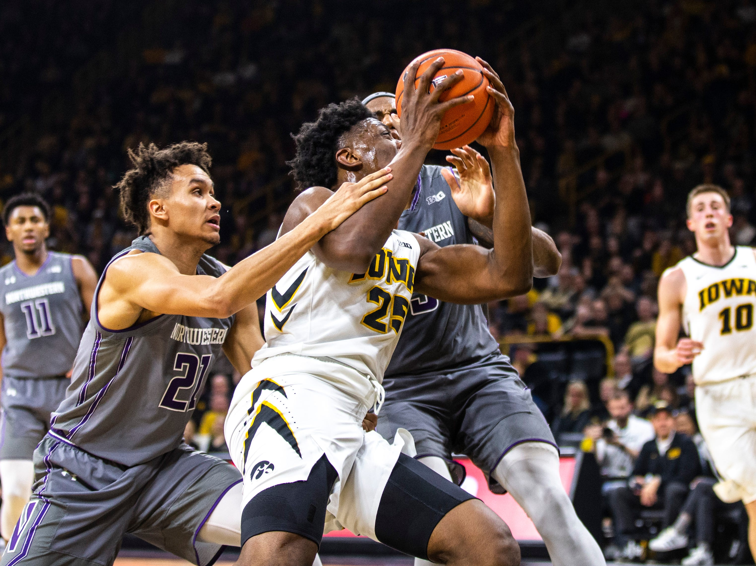 Iowa forward Tyler Cook (25) gets fouled by Northwestern forward A.J. Turner (21) during a NCAA Big Ten Conference men's basketball game on Sunday, Feb. 10, 2019 at Carver-Hawkeye Arena in Iowa City, Iowa.