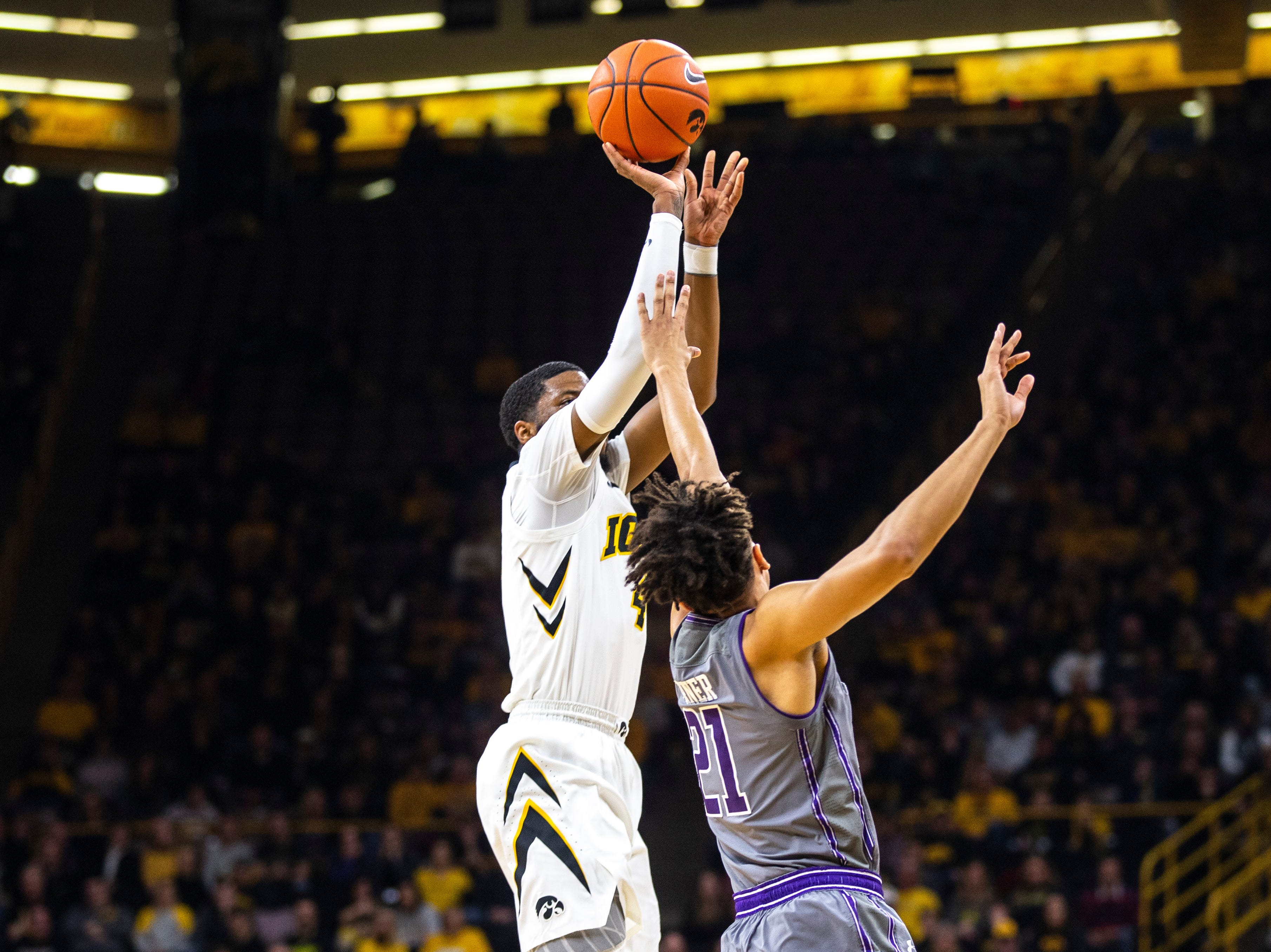 Iowa guard Isaiah Moss (4) attempts a 3-point basket while Northwestern forward A.J. Turner (21) defends during a NCAA Big Ten Conference men's basketball game on Sunday, Feb. 10, 2019 at Carver-Hawkeye Arena in Iowa City, Iowa.
