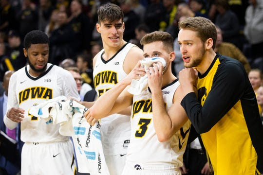 Iowa guard Jordan Bohannon (3) is embraced by Iowa forward Riley Till on the bench after making a 3-point basket to defeat Northwestern during a NCAA Big Ten Conference men's basketball game on Sunday, Feb. 10, 2019 at Carver-Hawkeye Arena in Iowa City, Iowa.