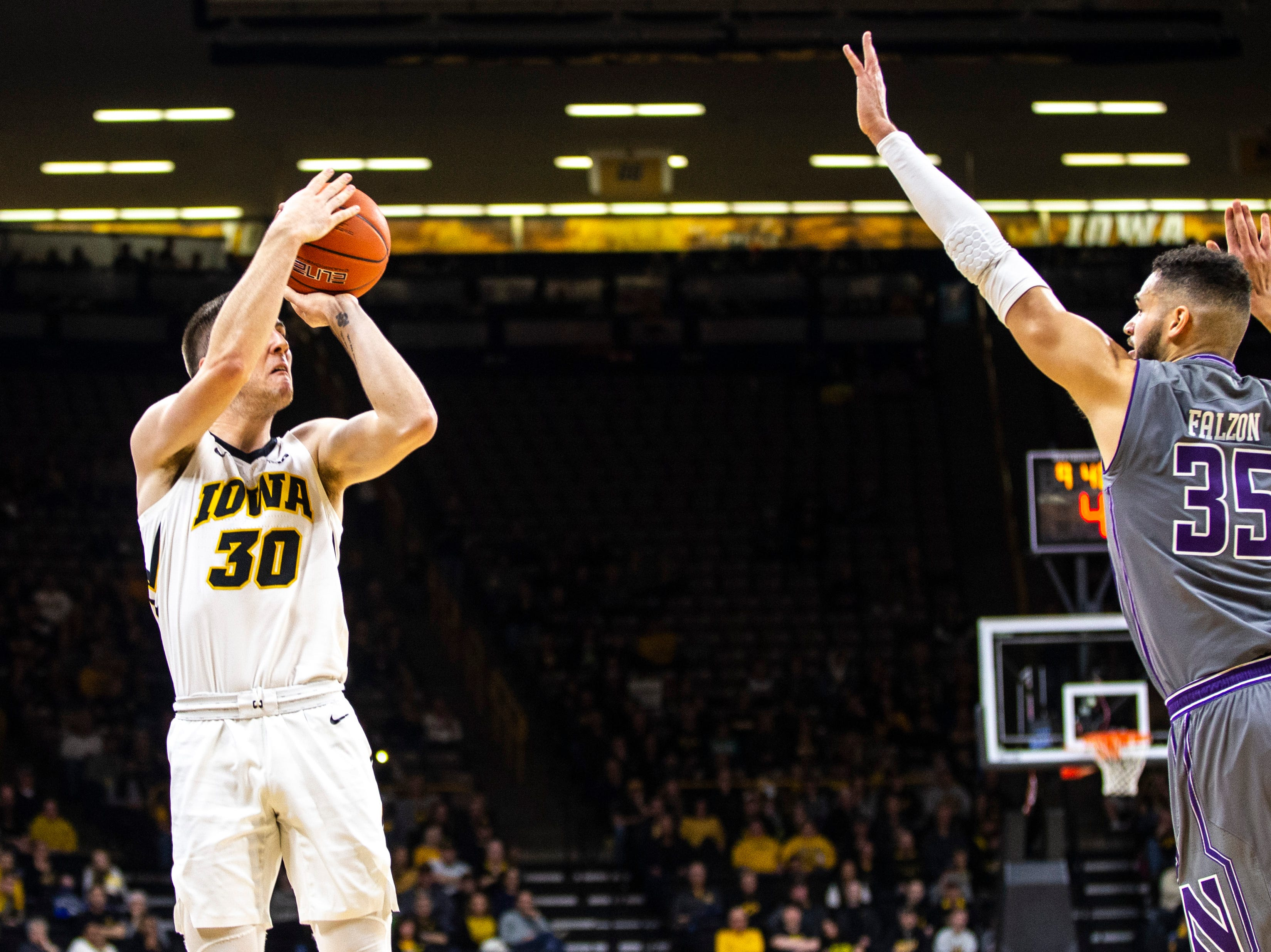 Iowa guard Connor McCaffery (30) shoots a 3-point basket while Northwestern forward Aaron Falzon defends during a NCAA Big Ten Conference men's basketball game on Sunday, Feb. 10, 2019 at Carver-Hawkeye Arena in Iowa City, Iowa.