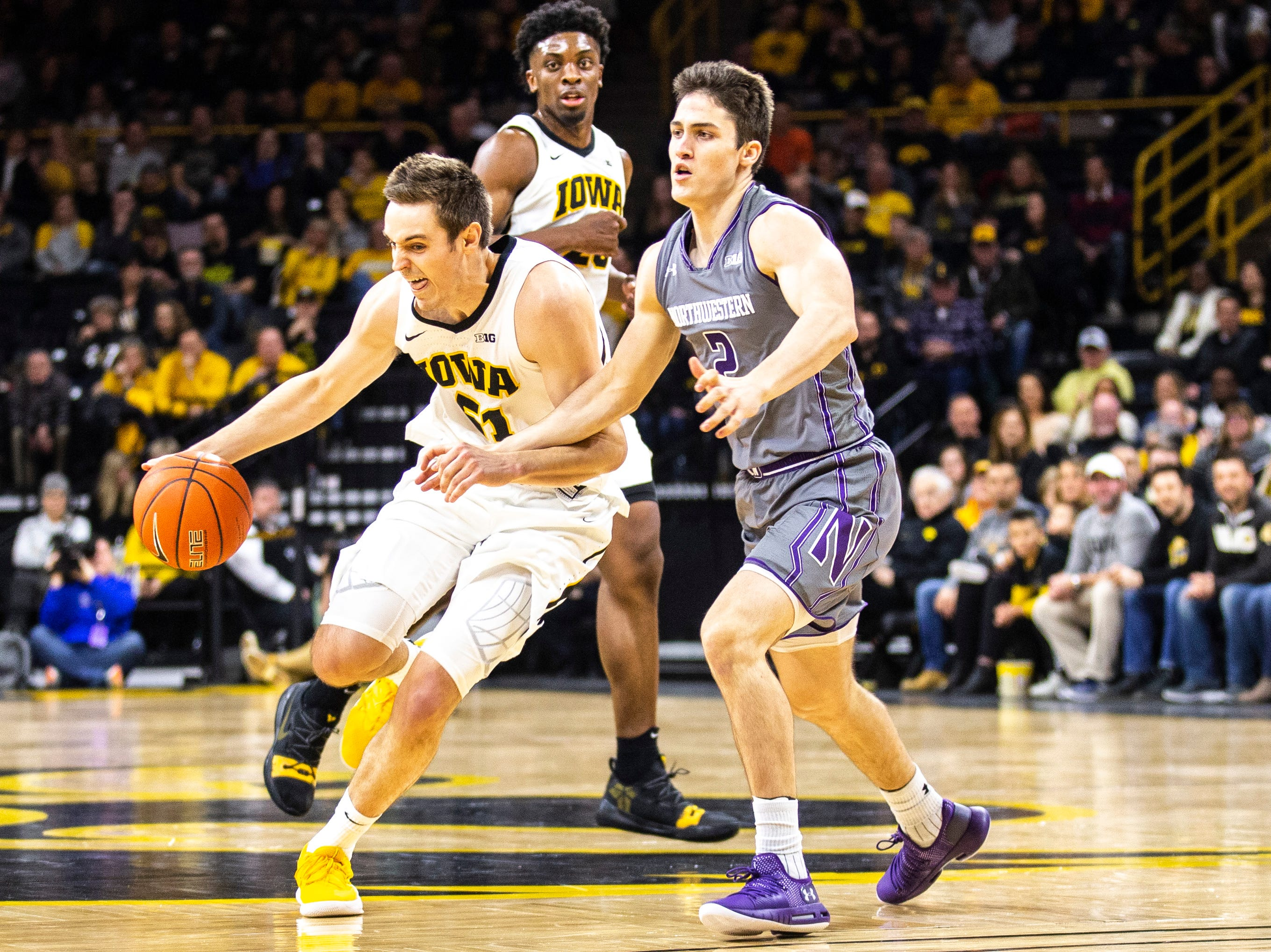 Iowa forward Nicholas Baer (51) drives to the basket while Northwestern guard Ryan Greer (2) defends during a NCAA Big Ten Conference men's basketball game on Sunday, Feb. 10, 2019 at Carver-Hawkeye Arena in Iowa City, Iowa.
