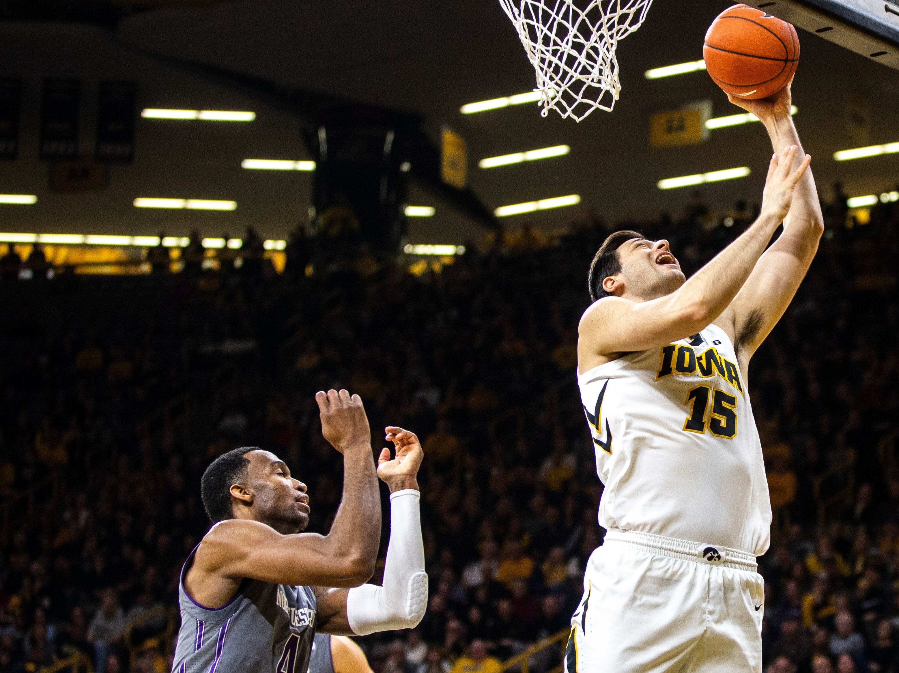 Iowa forward Ryan Kriener (15) drives to the basket while Northwestern forward Vic Law defends during a NCAA Big Ten Conference men's basketball game on Sunday, Feb. 10, 2019 at Carver-Hawkeye Arena in Iowa City, Iowa.
