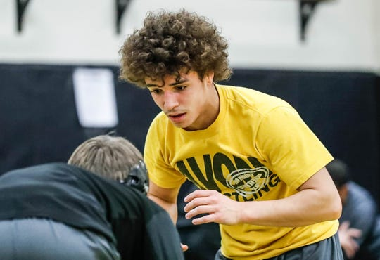 Avon wrestlers Asa Garcia, yellow shirt, and Tyler Conley, black shirt, practice wrestling moves during a team practice in the wrestling room at Avon High School, on Monday, Jan. 11, 2019. Asa Garcia, an Avon H.S. senior and two-time state wrestling champ is chasing his third state title.