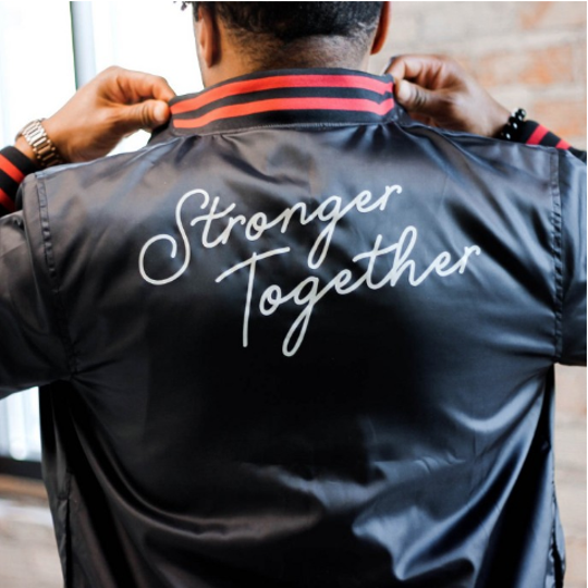 Le'Spencer Walker wearing bomber jacket inspired by the Black History Month collection by Target.