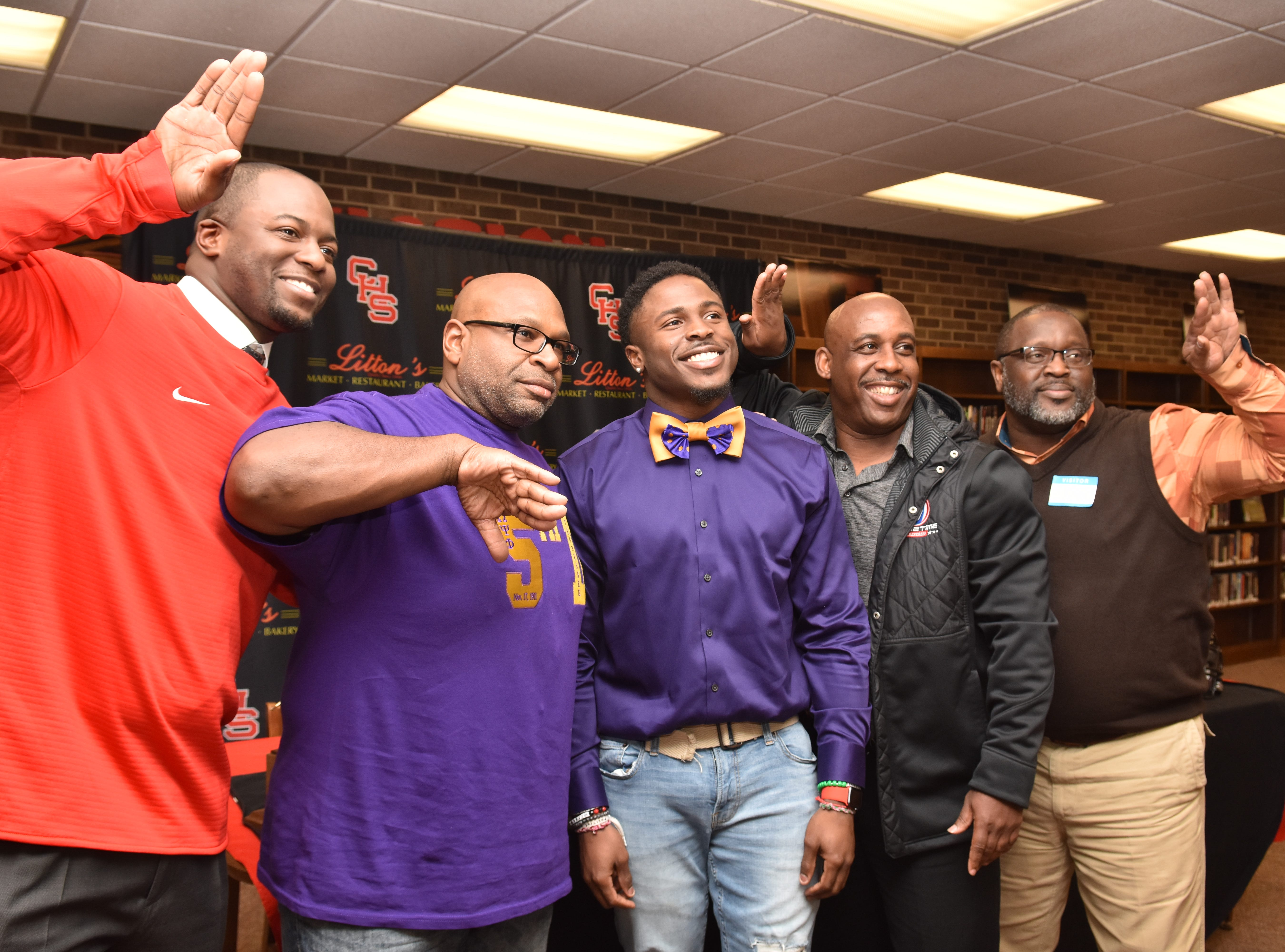 """Talons Up"". Central High coach Bryson Rosser, left, celebrates with Xavier Washington and family as Washington prepares to sign with Tennessee Tech on Monday, Feb. 11, 2019."