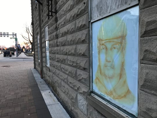 A poster of a suspect in the slaying of Abby Williams and Libby German, eighth-graders at Delphi Community Middle School, starts to fade in the window of a building at Main and Washington streets on the Carroll County Courthouse square in Delphi two years after the girls were killed on Feb. 13, 2017.