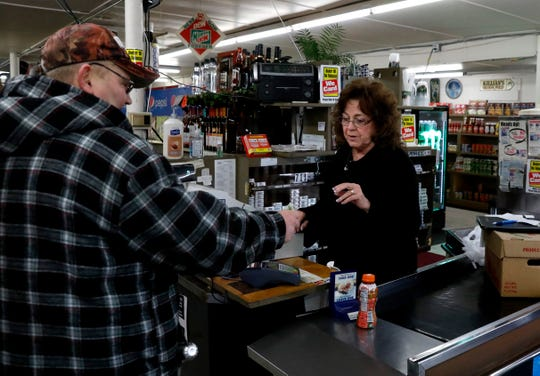Kathy Hartley runs the cash register at Fred's Market on Reese Avenue. Hartley and her husband Fred Drumm purchased the small grocery store in 1976.