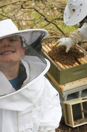 Jonah Kish, 8, from Brighton, smiles while in a beekeeper suit as his father Steven puts 10,000 bees into Jonah's hive in 2016. Jonah was honored Monday by the Brighton Area Schools Board of Education for he and his family's effort to sell leftover honey to raise money buy toys for children at C.S. Mott Children's Hospital in Ann Arbor  for Christmas last year.