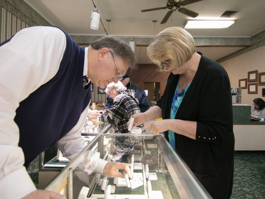 Bill King shows customer Nina Sgriccia a ruby and diamond pendant at Yax Jewelers in Howell Monday, Feb. 11, 2019.