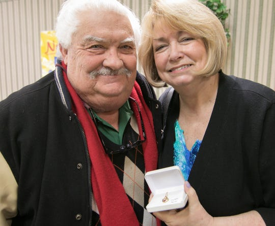 David and Nina Sgriccia hold up a ruby and diamond pendant the couple selected at Yax Jewelers Monday, Feb. 11, 2019 as a gift to Nina for Valentine's Day.