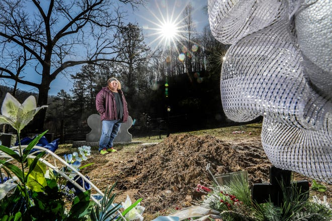 Brandy Stafford stands at the grave of her brother, James Ramey, who is buried in a family cemetery just outside of Inez, Kentucky.  Ramey died after contracting Hepatitis A.